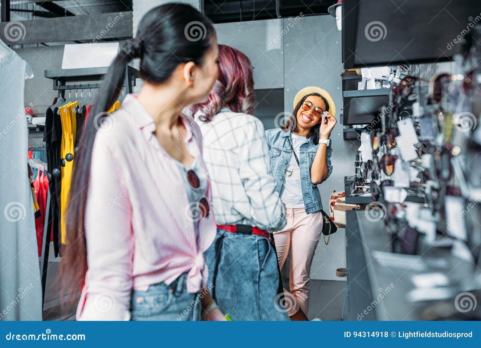 Filles multiculturelles de hippie choisissant des lunettes de soleil dans  la boutique 3183a04ddce1