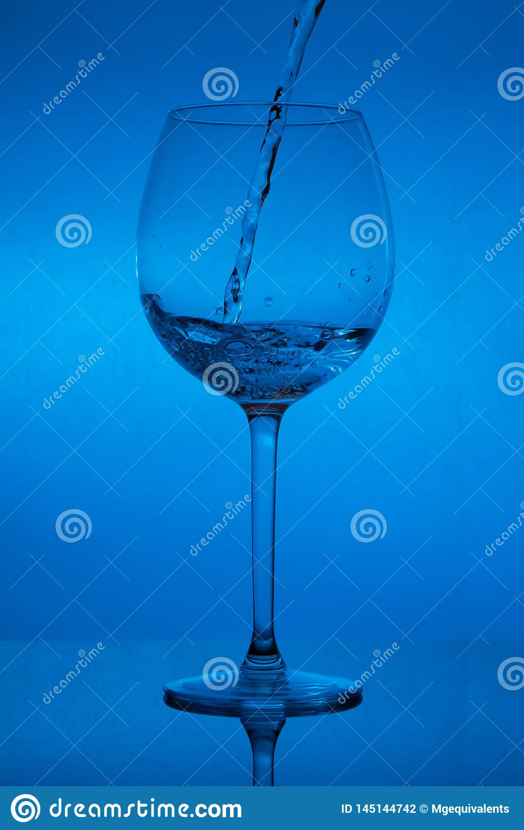 Filling the glass, pouring wineglass on blue background