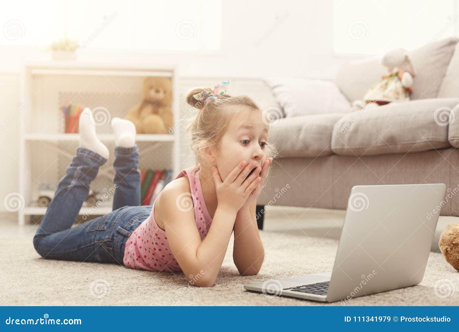 Film de observation occasionnel effrayé de petite fille sur l ordinateur portable tout en se trouvant sur le plancher à la maison