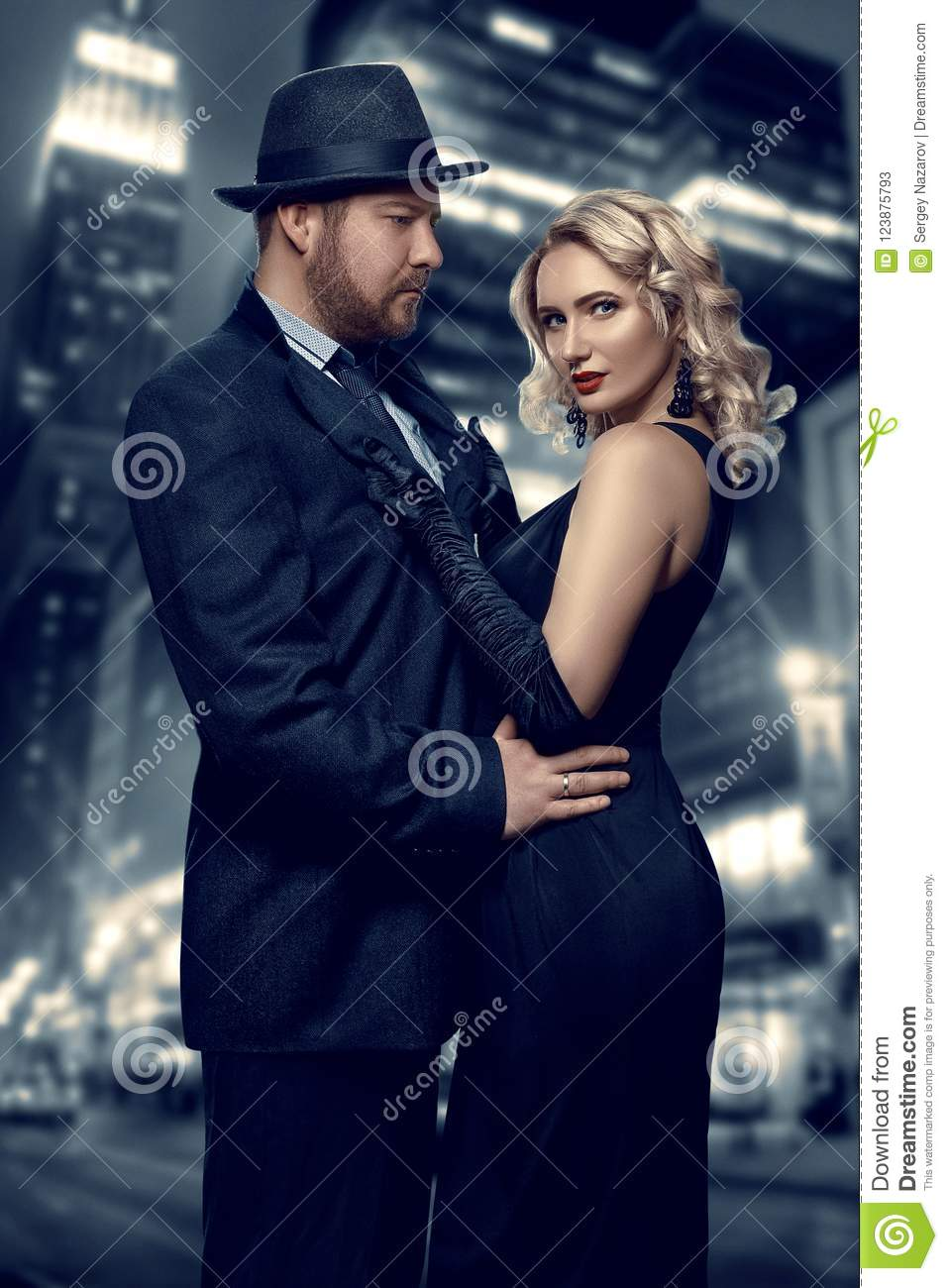 Film noir. Detective man in a raincoat and hat and a dangerous woman with red lips in black dress. Couple stands against