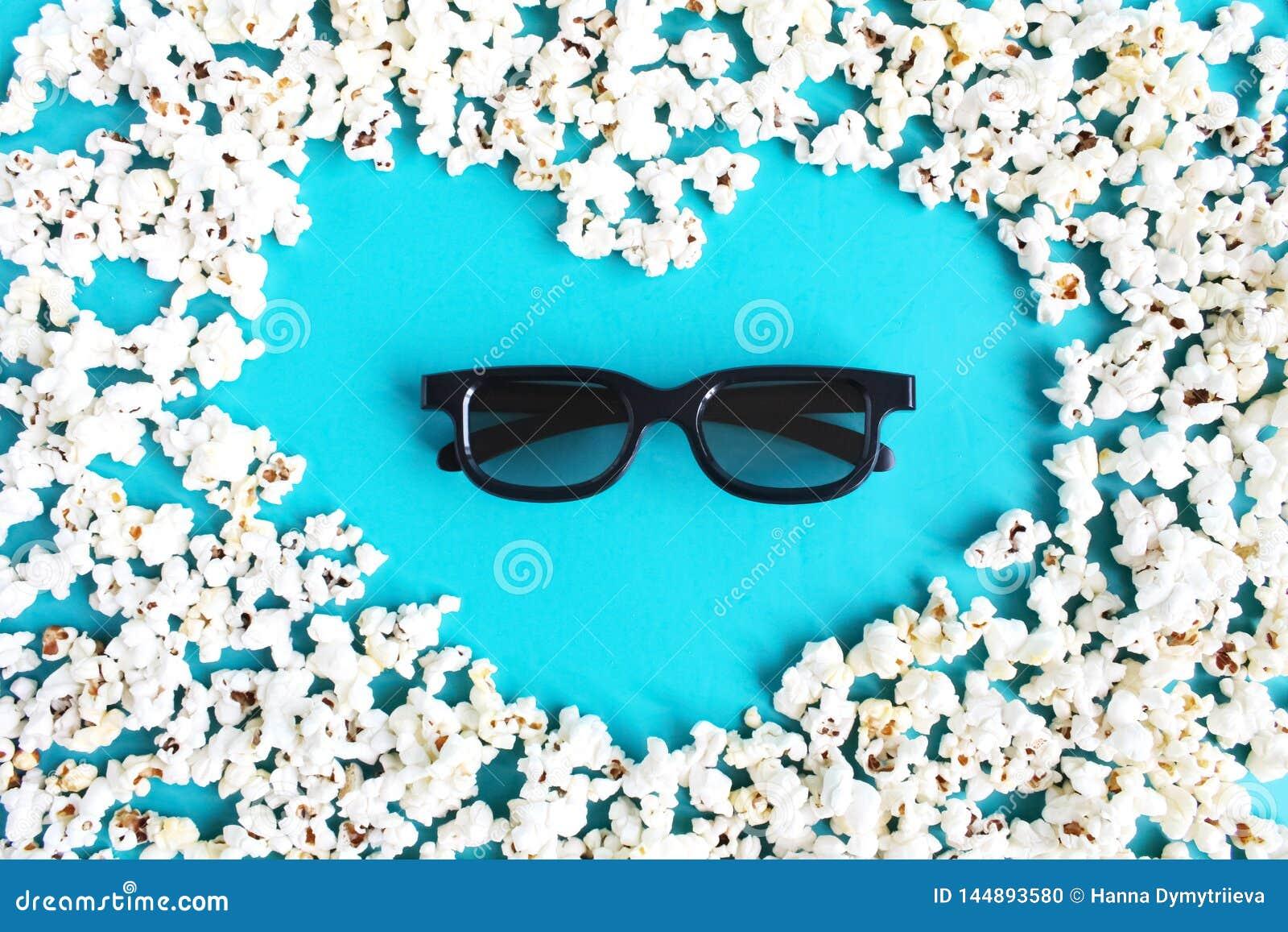 Film, passatempo, spettacolo e cinema di amore di concetto Forma del popcorn di cuore e di vetri 3d su fondo blu