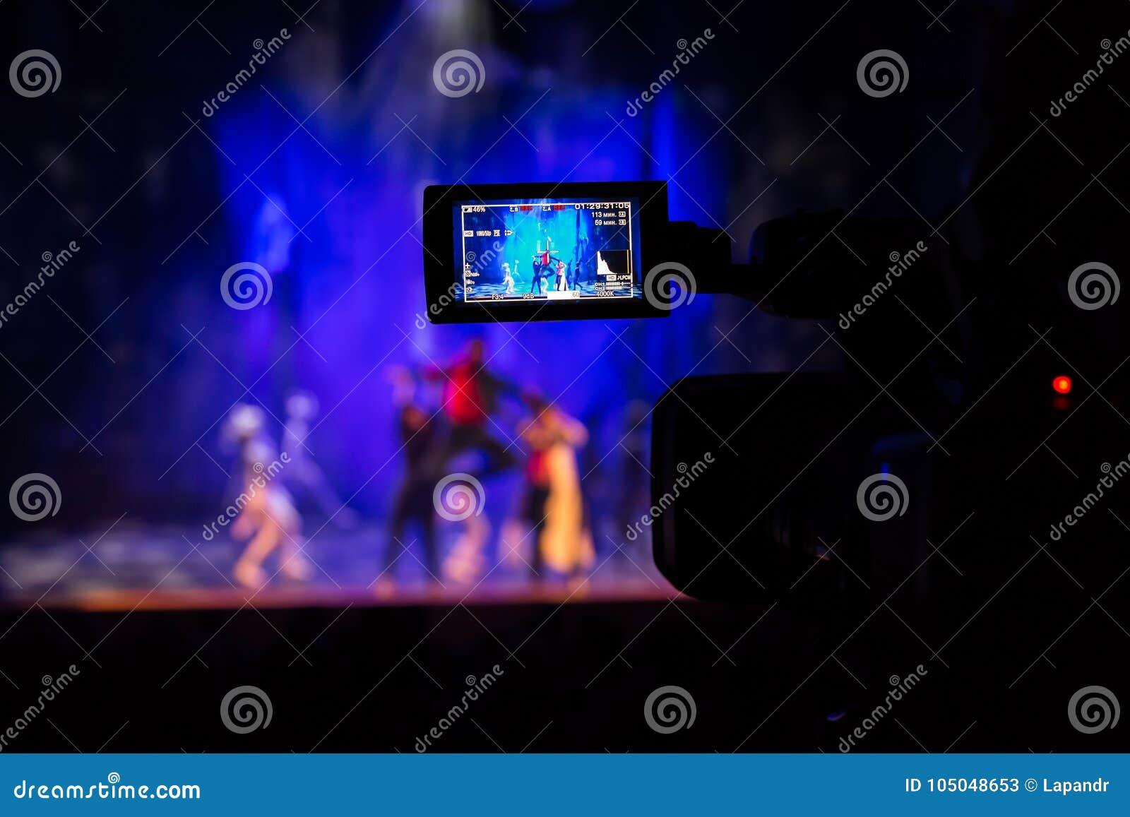 Filmando a mostra do auditório Visor do LCD na câmara de vídeo Desempenho teatral Os atores na fase