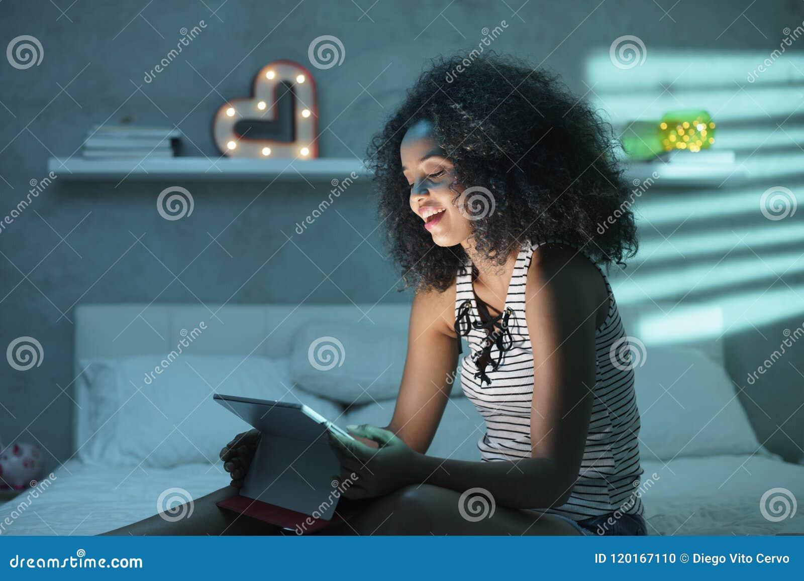 Filme de observação da mulher negra nova com o portátil na noite