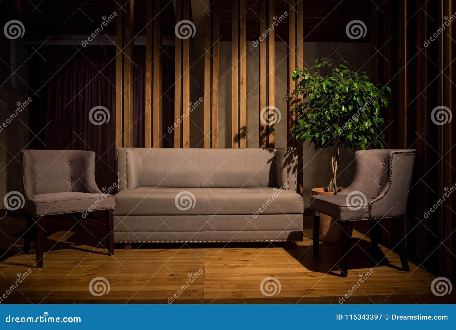 Filmiskt ljus En grå soffa och två gråa stolar på träben står på ett brunt träpodium