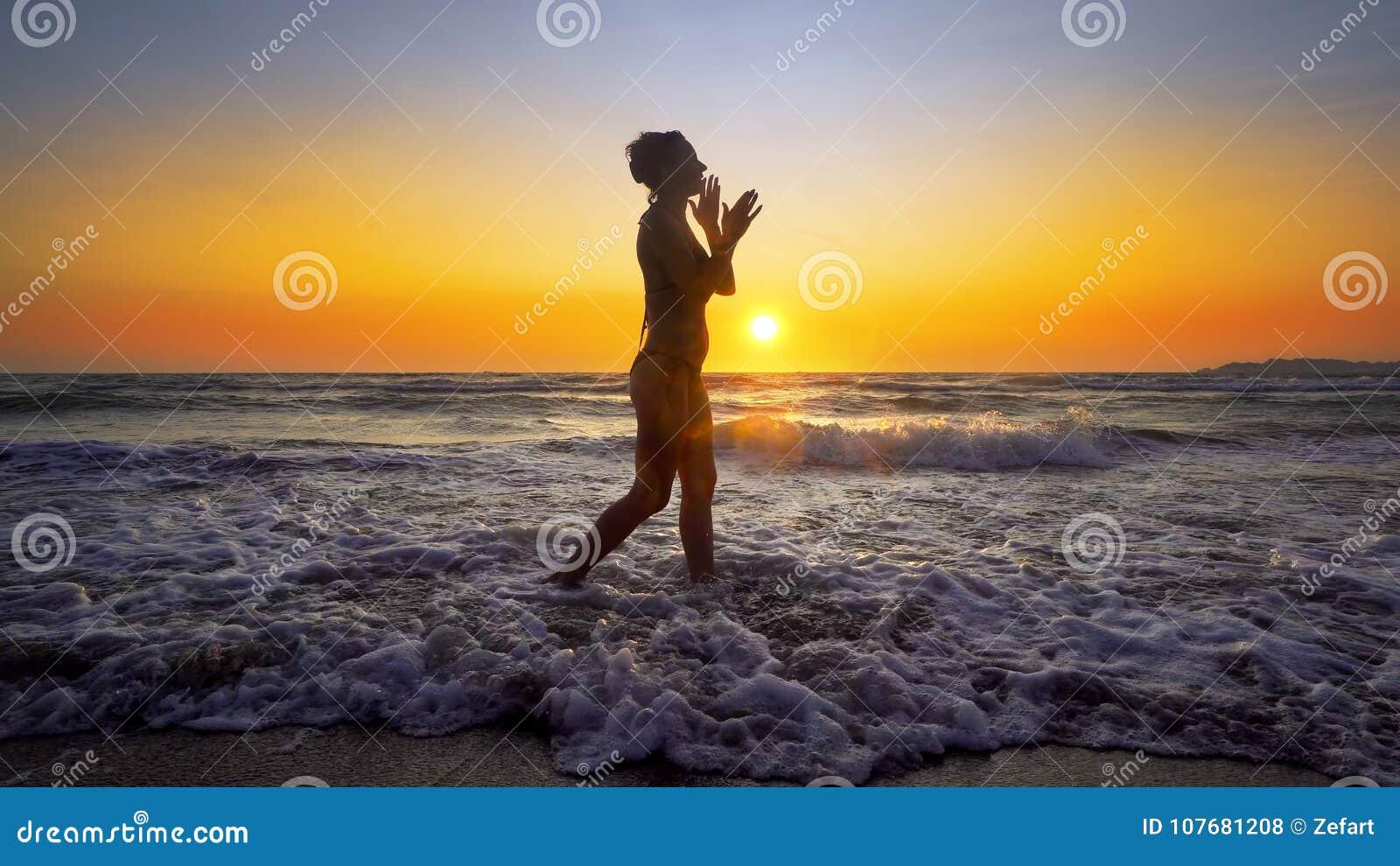Filmiskt skott av kvinnan som går på vatten på solnedgången