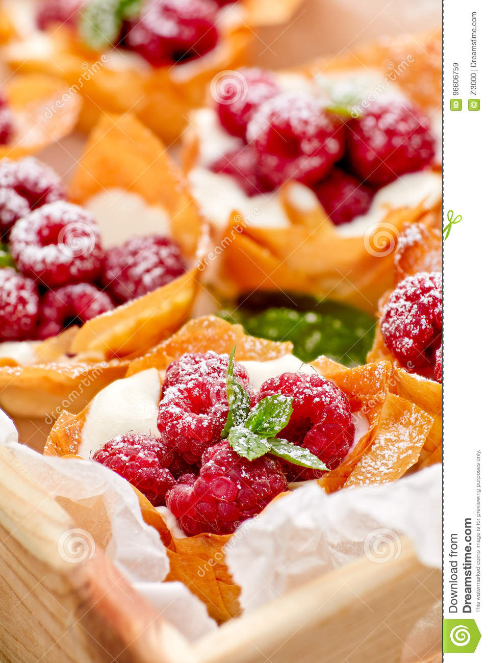 Filo cups with Mascarpone filling topped with raspberries , delicious dessert