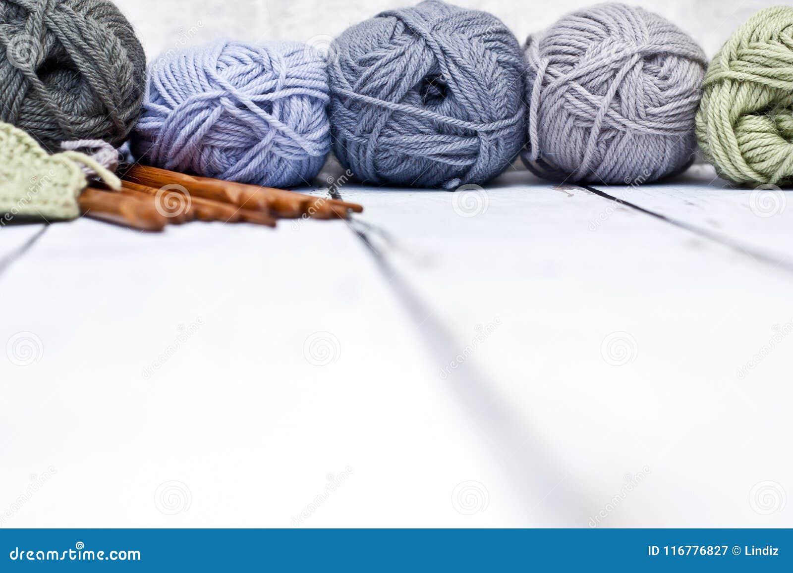 Fils dans le panier avec des crochets de crochet dans des couleurs harmonieuses tricotant, approvisionnements faisants du crochet