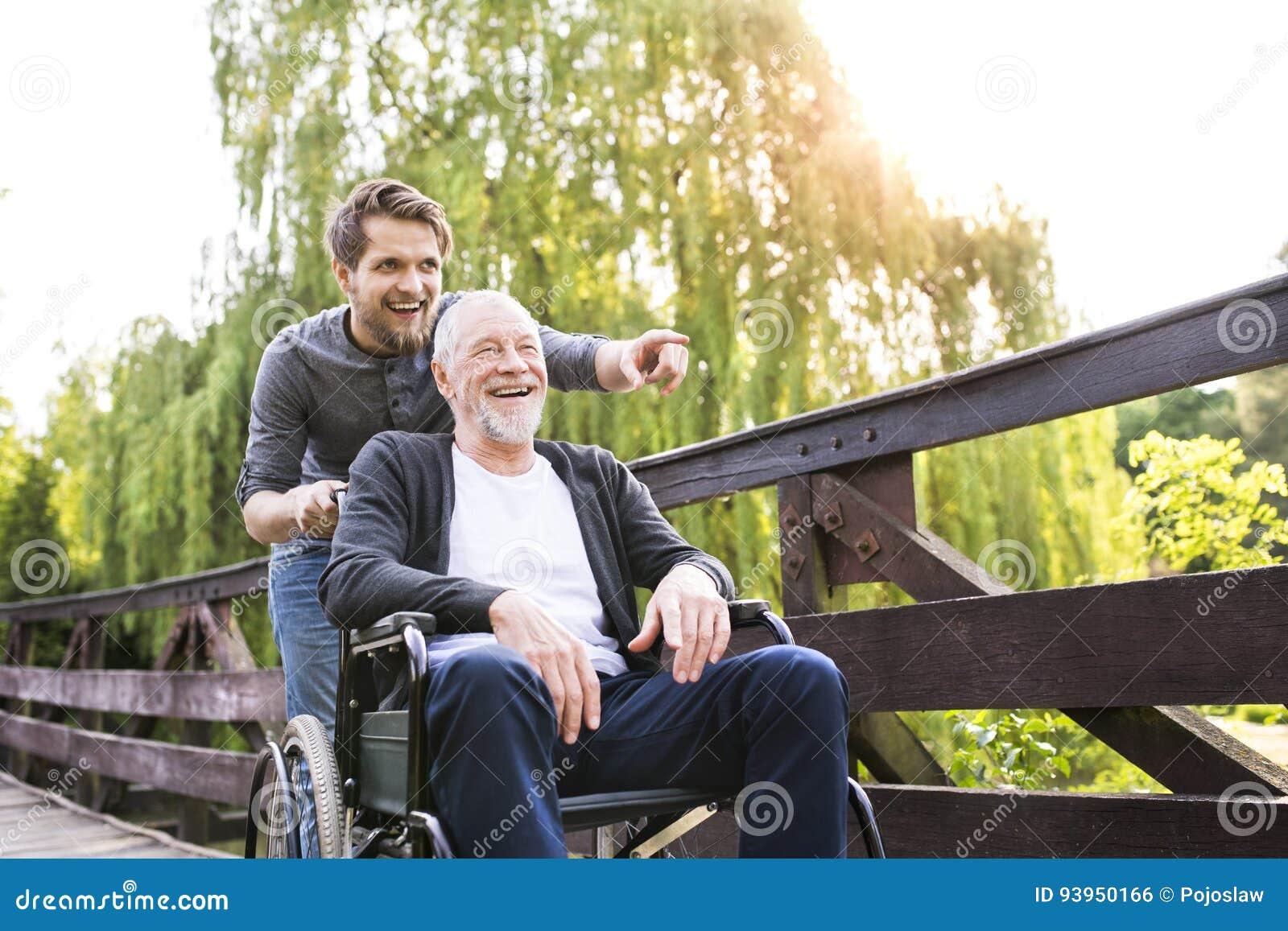 Fils de hippie marchant avec le père handicapé dans le fauteuil roulant au parc