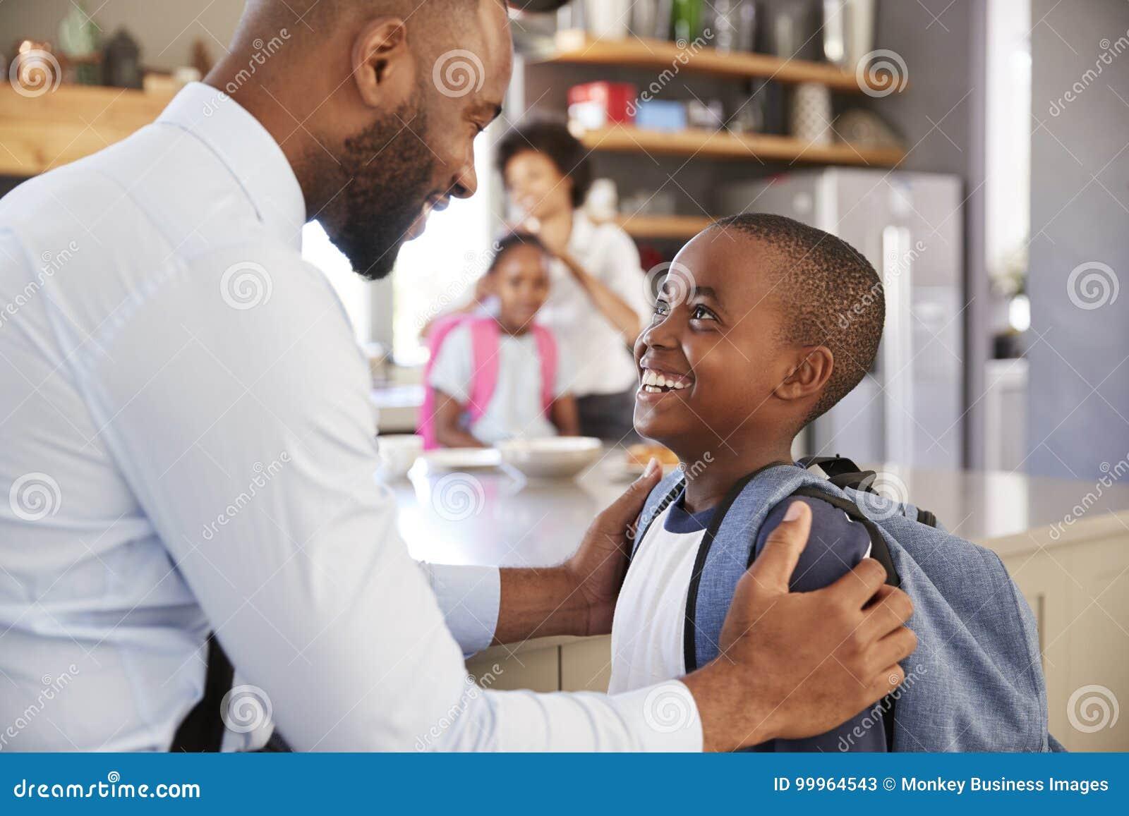 Fils de Saying Goodbye To de père comme il part pour l école