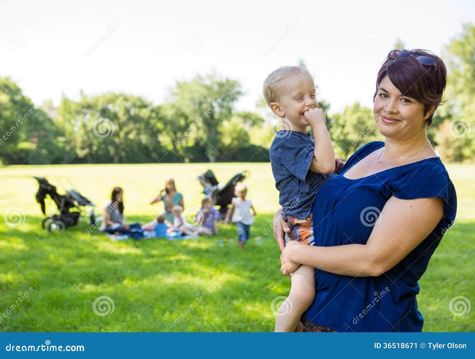 Fils de transport de mère heureuse en parc