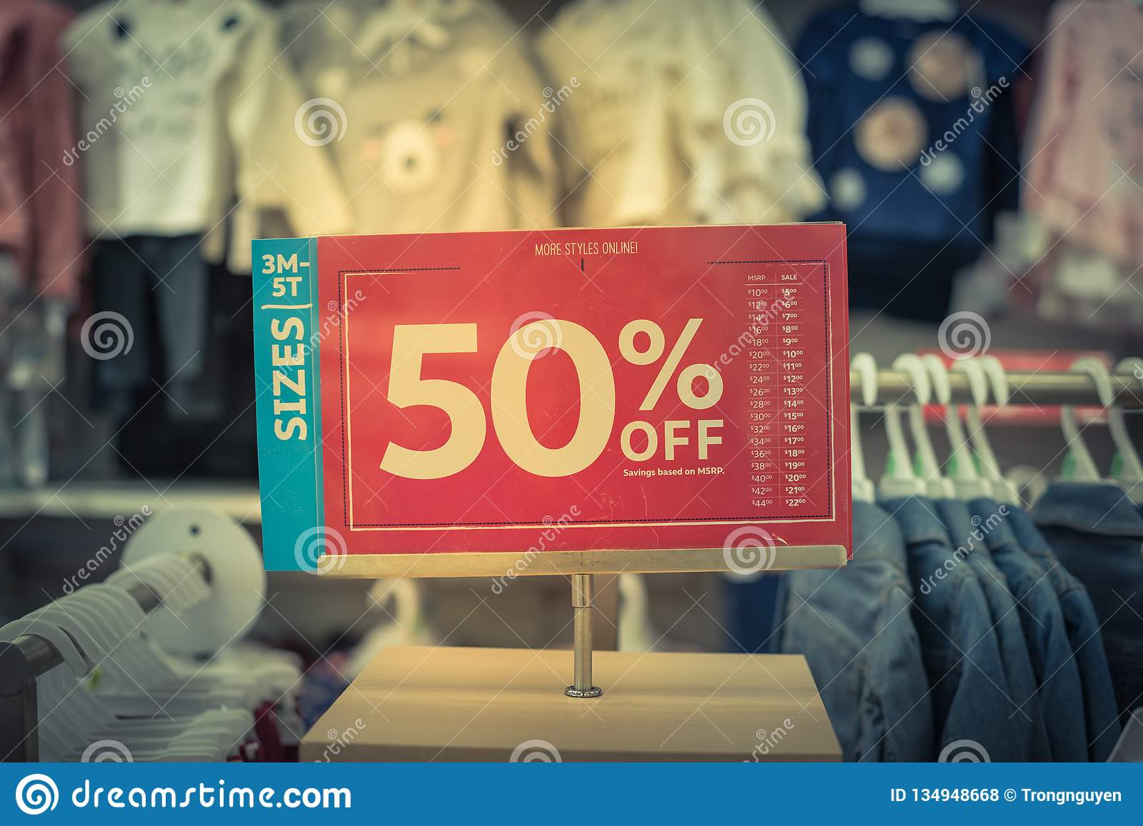 Filtered Image 50 Percent Off Sale Sign Over Clothes At ...