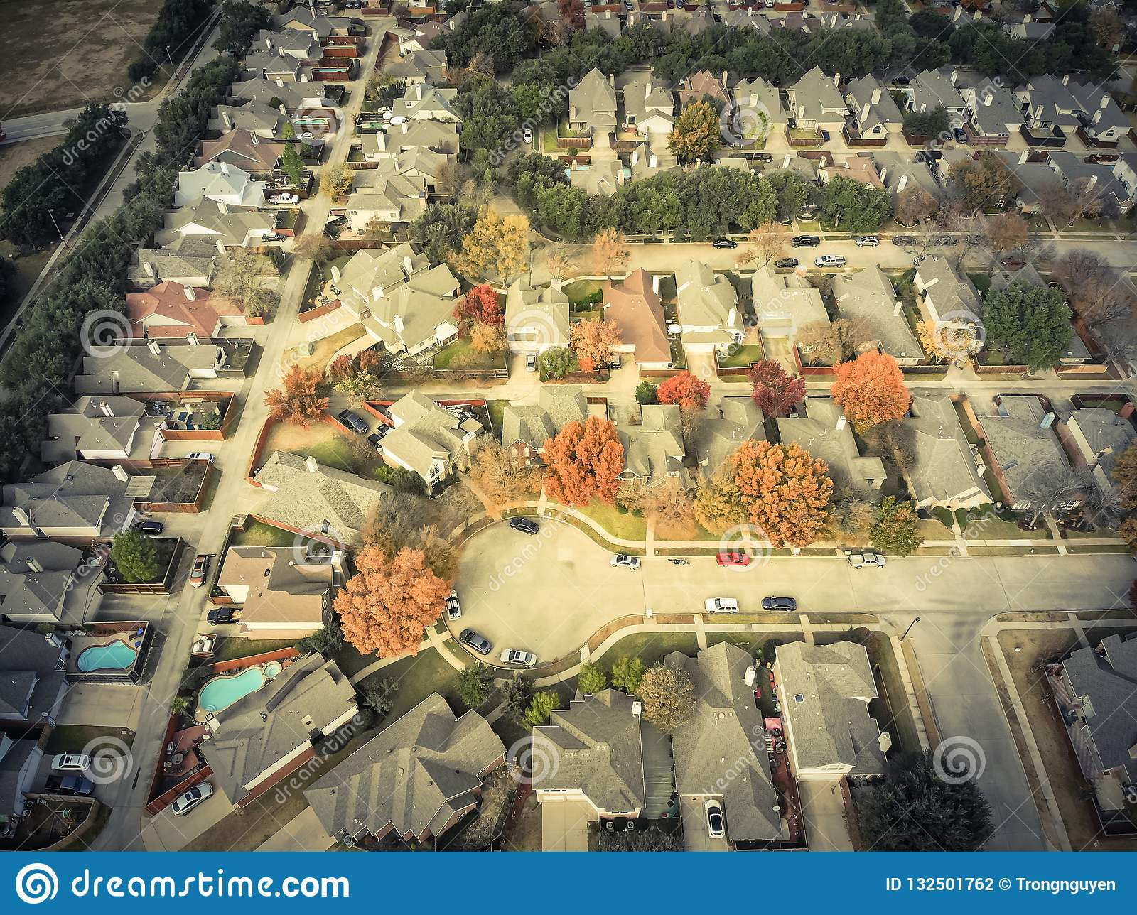 Filtered image top view cul-de-sac street in residential neighborhood with colorful autumn leaves