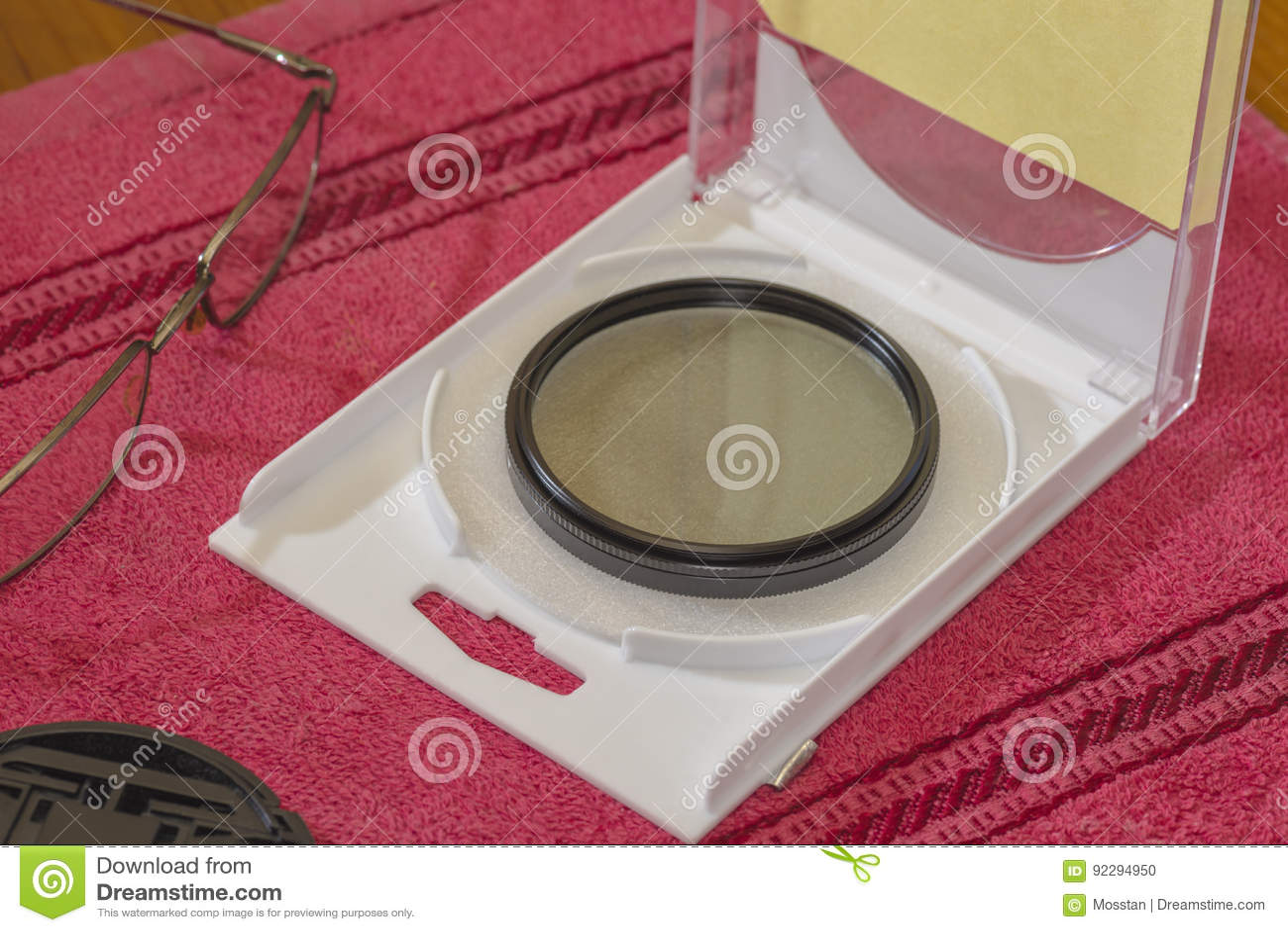 Filtro COMPLETO di polarizzazione per la lente sulla tavola in una scatola aperta