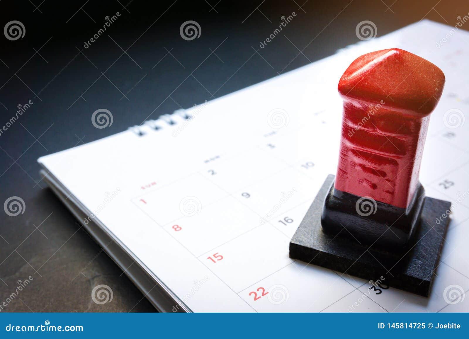 Fim acima da caixa vermelha do cargo do brinquedo no calendário mensal do planejador no fundo preto Programa??o do calend?rio do
