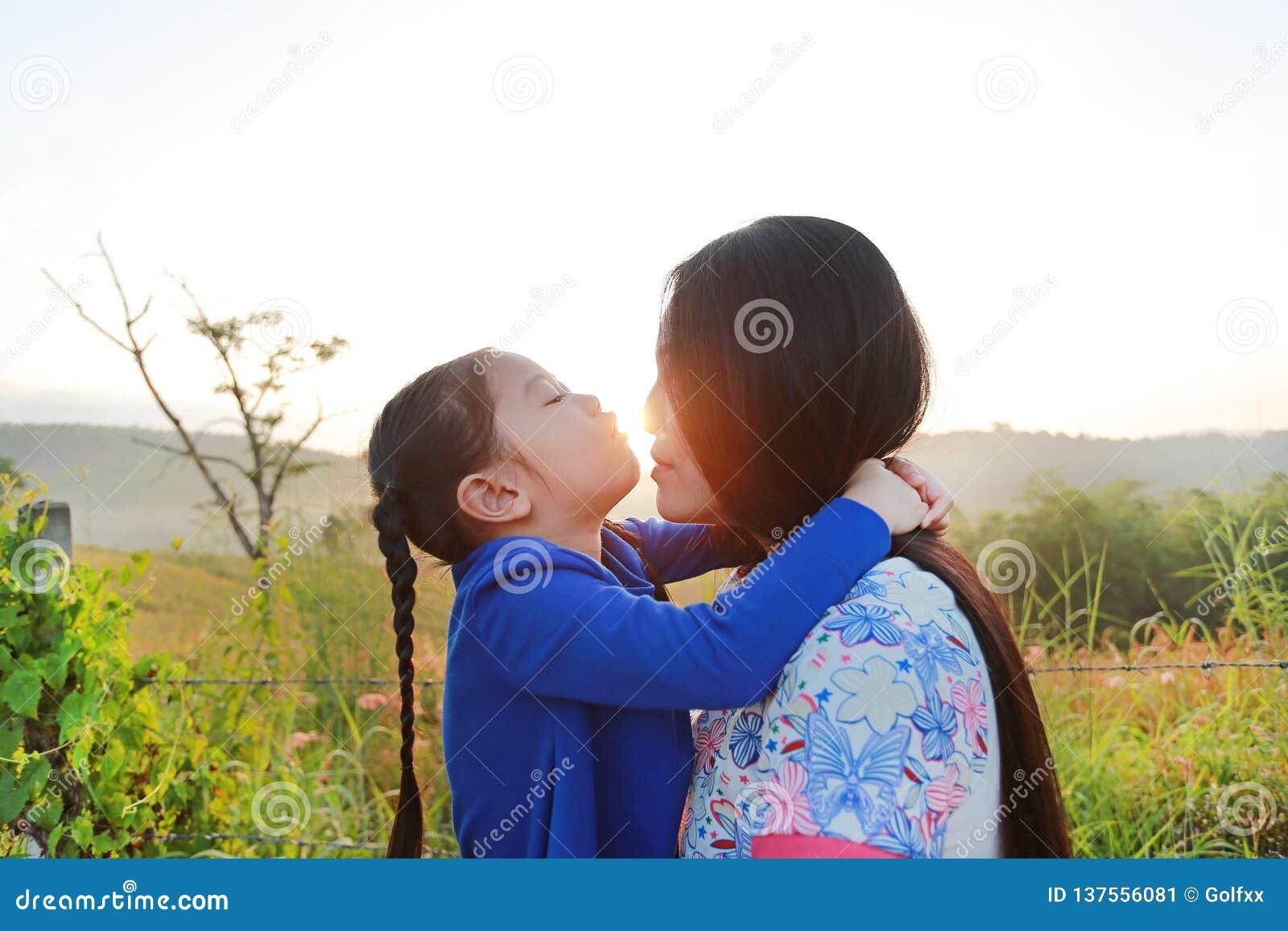 Fim acima da mãe asiática e das filhas que beijam no campo do prado no nascer do sol da manhã