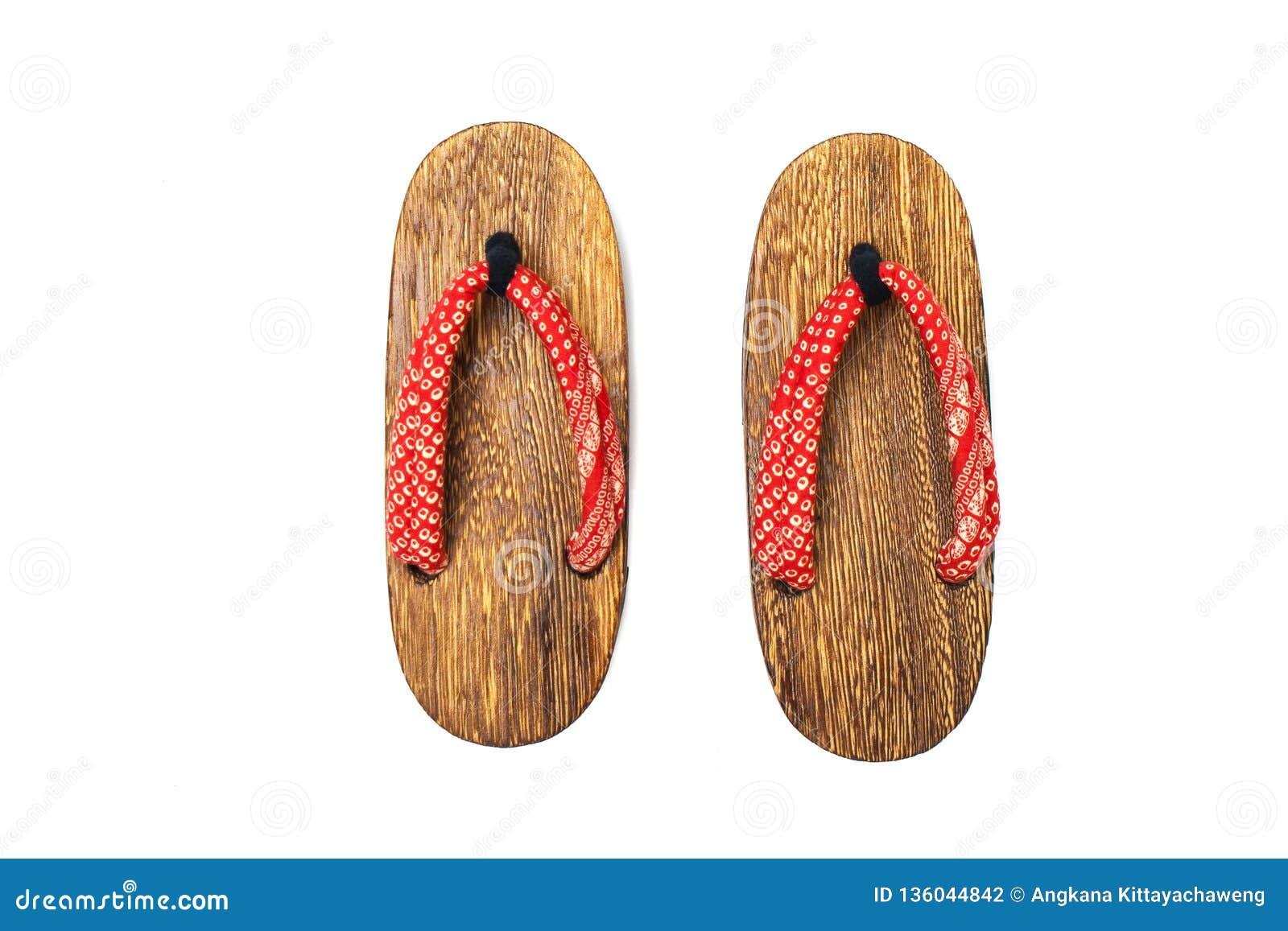 Fim acima da sandália japonesa de madeira usada velha isolada no fundo branco