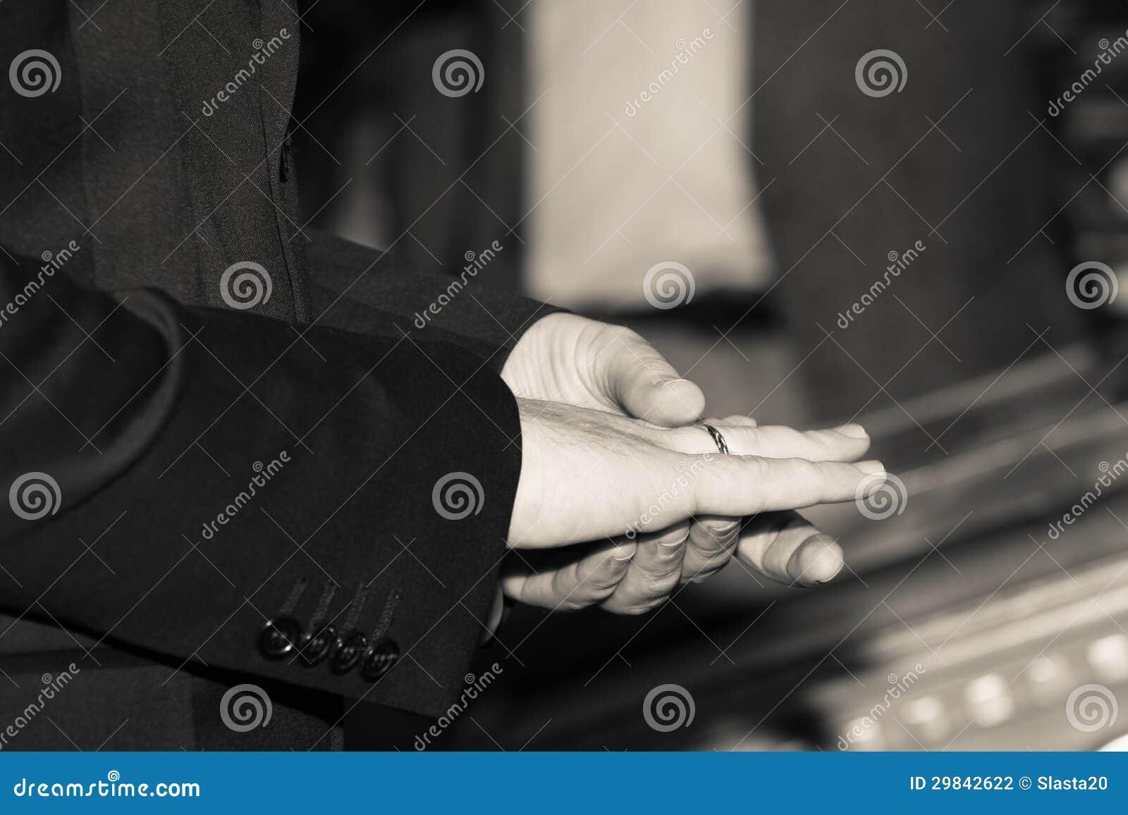 Mãos do homem da elegância com aliança de casamento