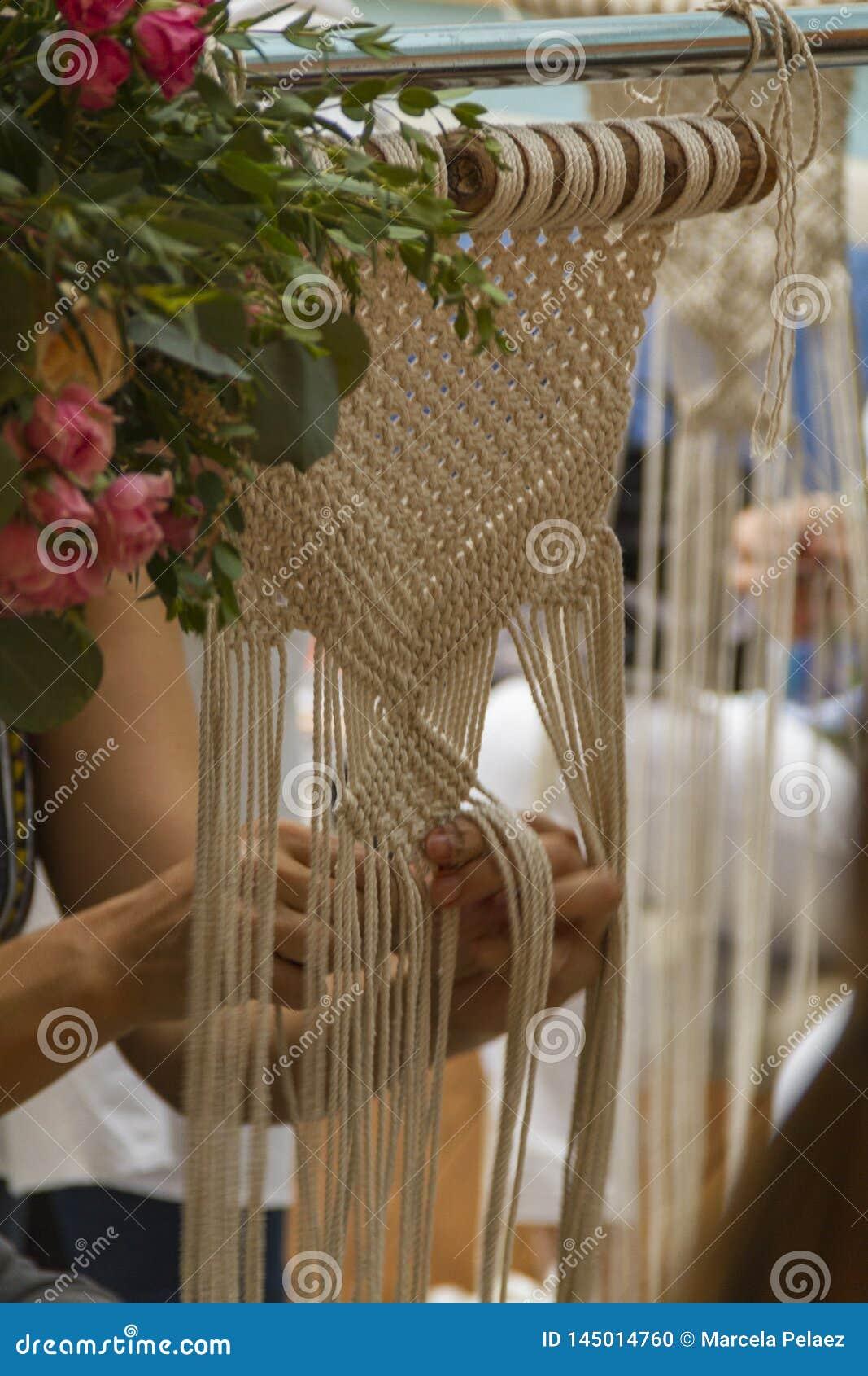 Fim acima das mãos que tecem a tapeçaria do macramê com linha bege