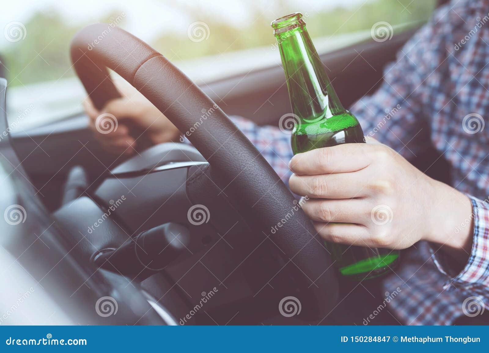 Fim acima de homem novo bêbado da mão ao conduzir um carro com uma garrafa da cerveja Bebida do ` t de Don e conceito da moviment