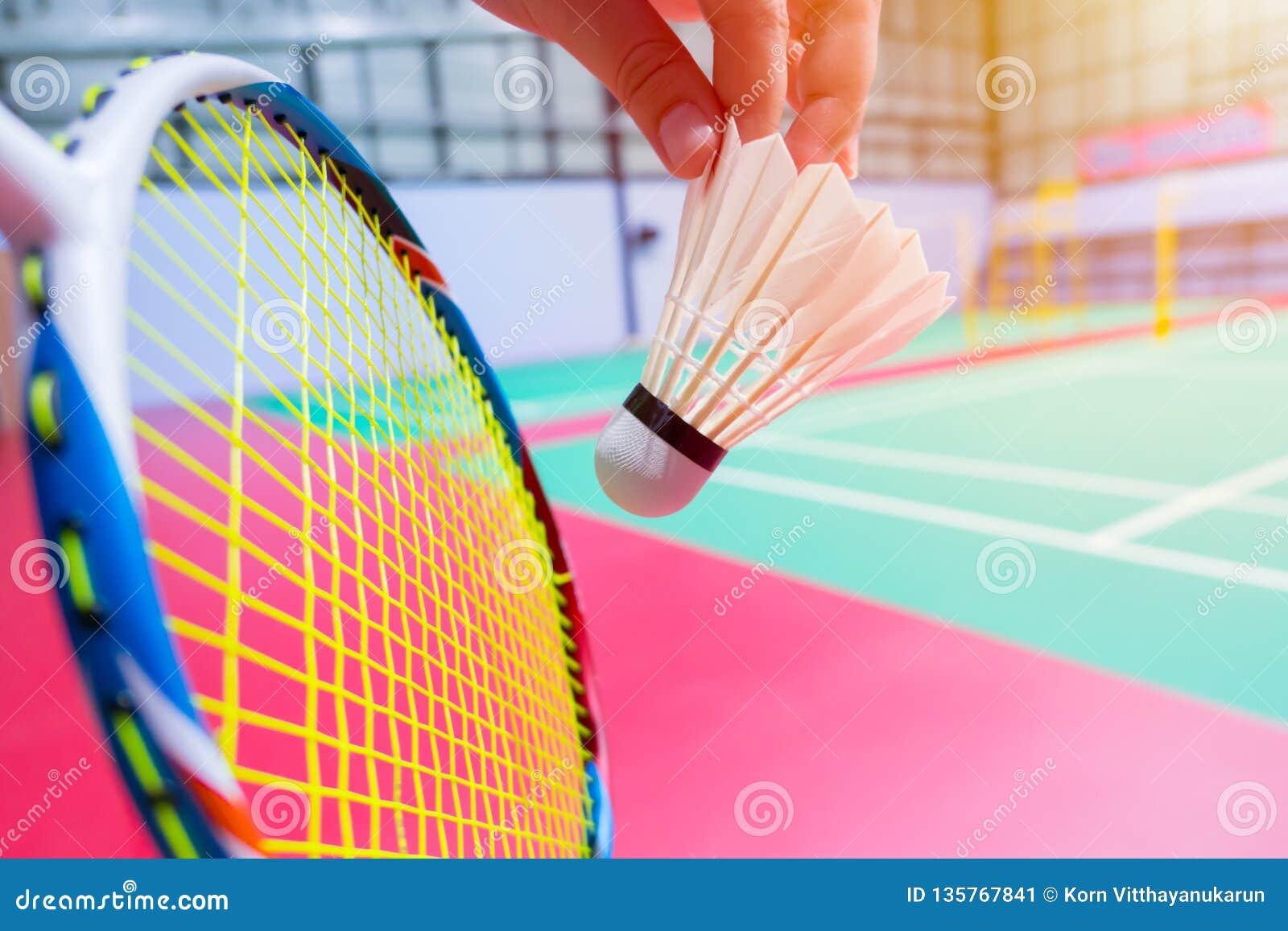 Fim acima do fundo da corte de badminton da peteca do badminton do saque da posse da mão