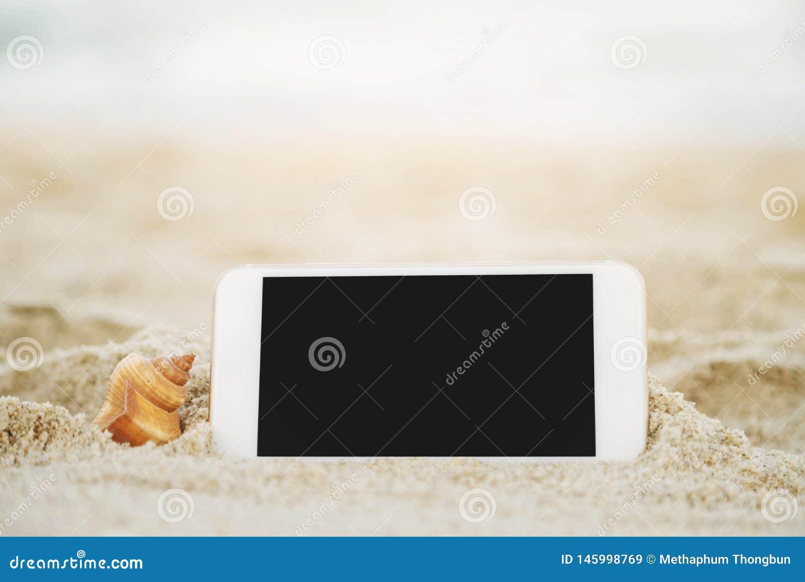 Fim acima do homem dos povos da mão que guarda o telefone esperto móvel branco na praia