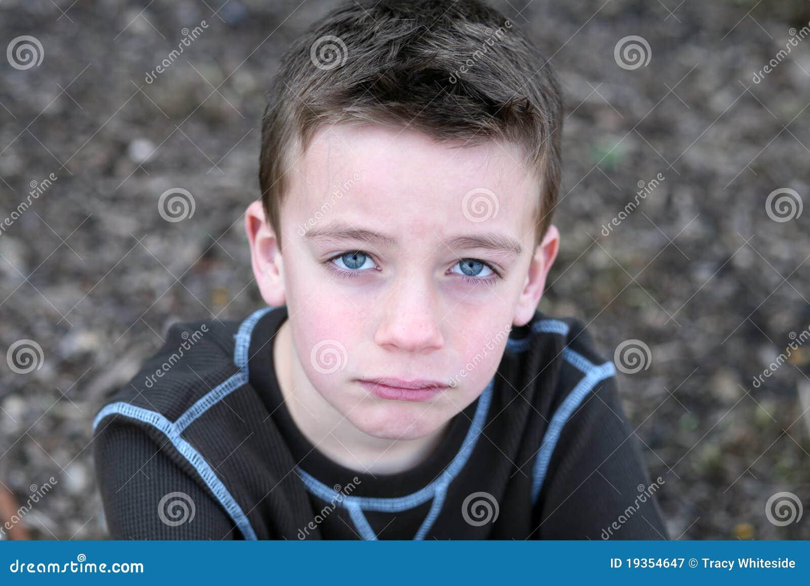 Fim acima do menino bonito com face triste