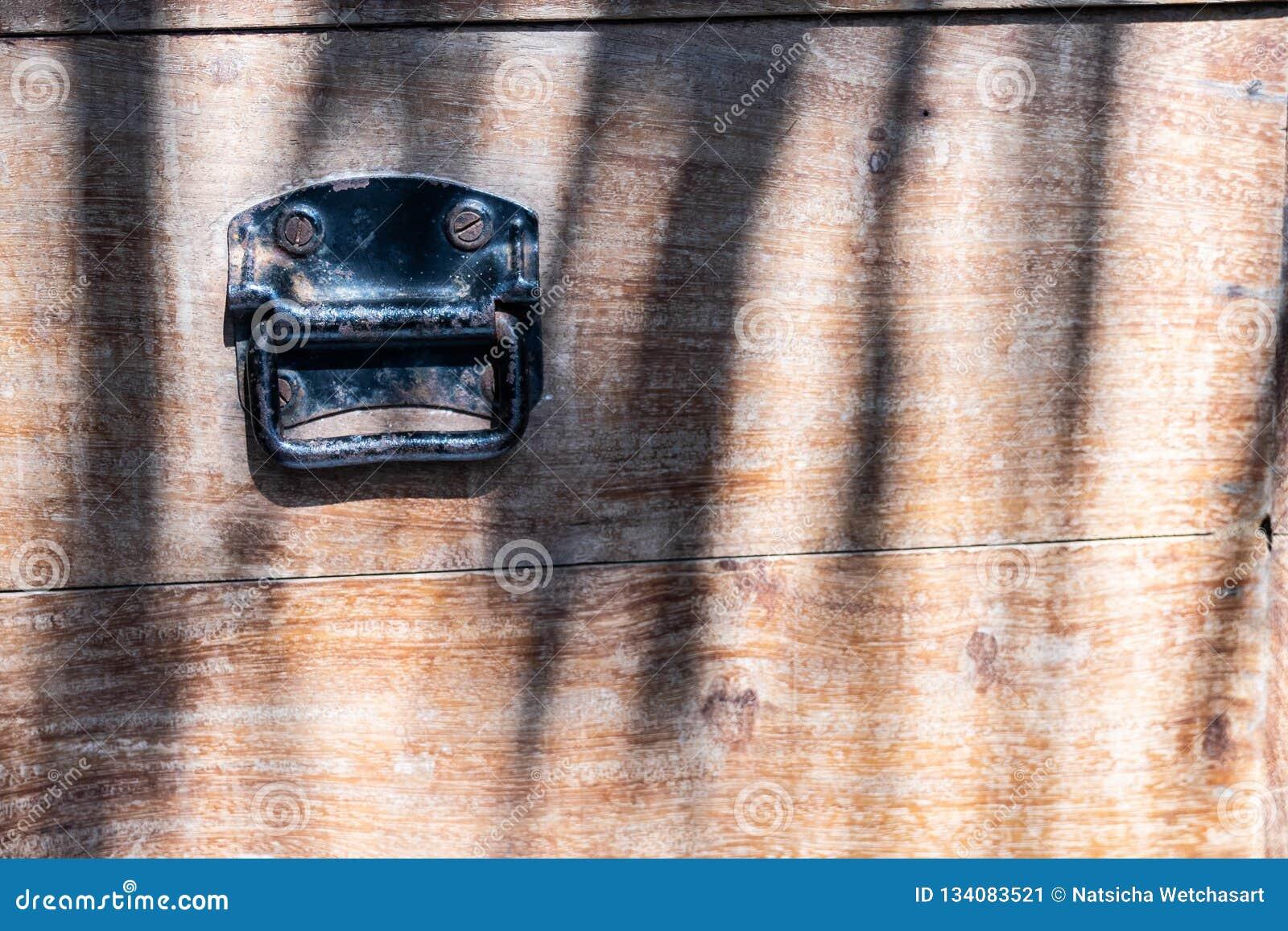 Fim acima do punho oxidado preto do metal do vintage no fundo da caixa de madeira