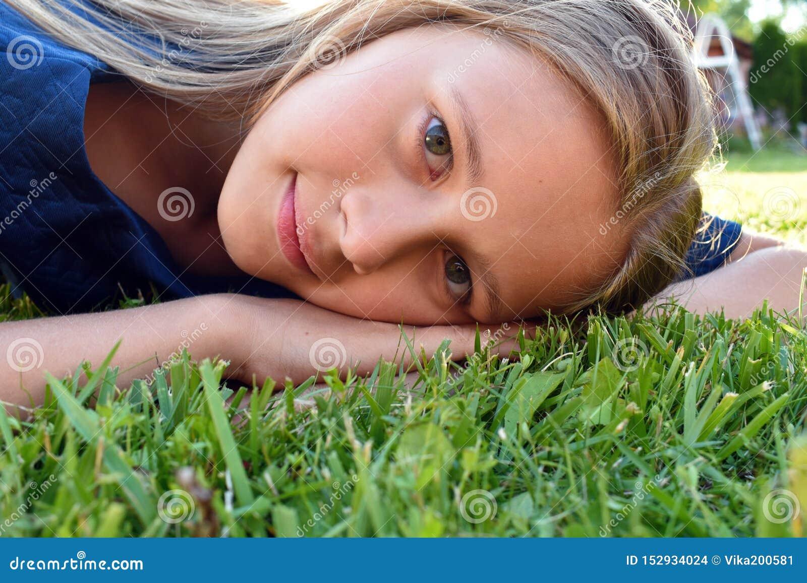 Fim bonito da moça acima na grama verde no verão