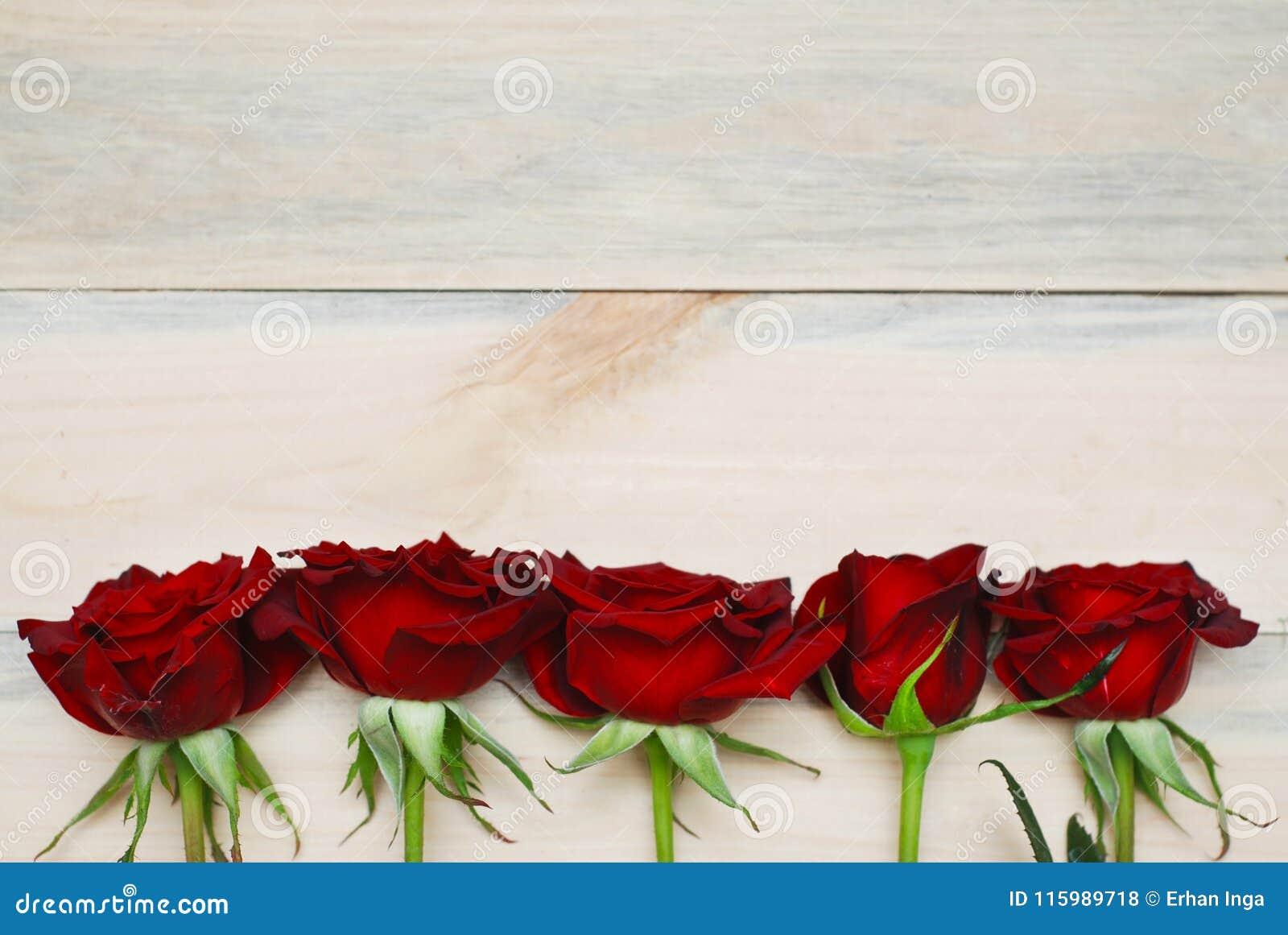 Fim vermelho de Rosess acima sobre o fundo Textured de madeira
