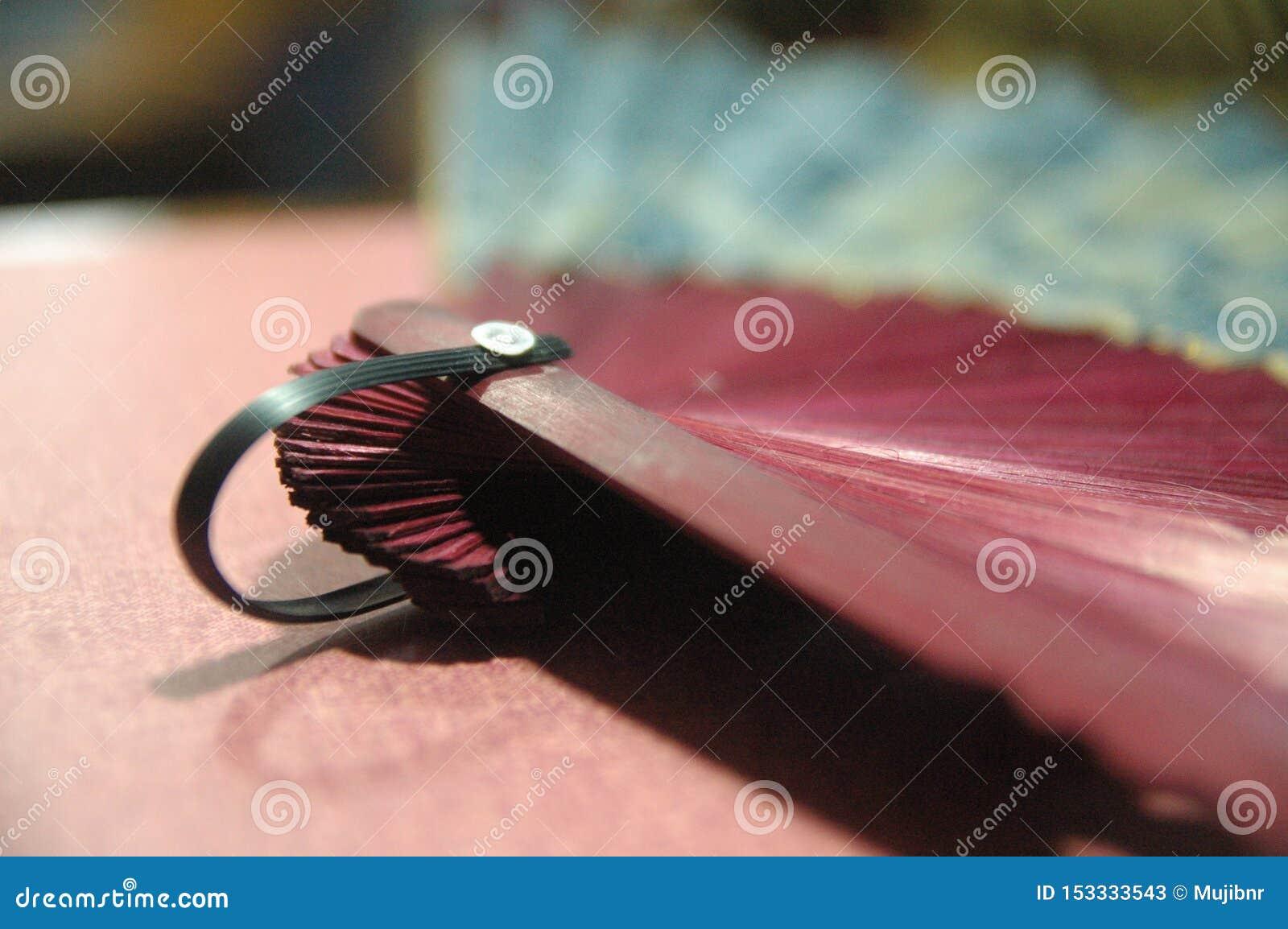 Fin en bois de couleur rouge de fan de main de femme