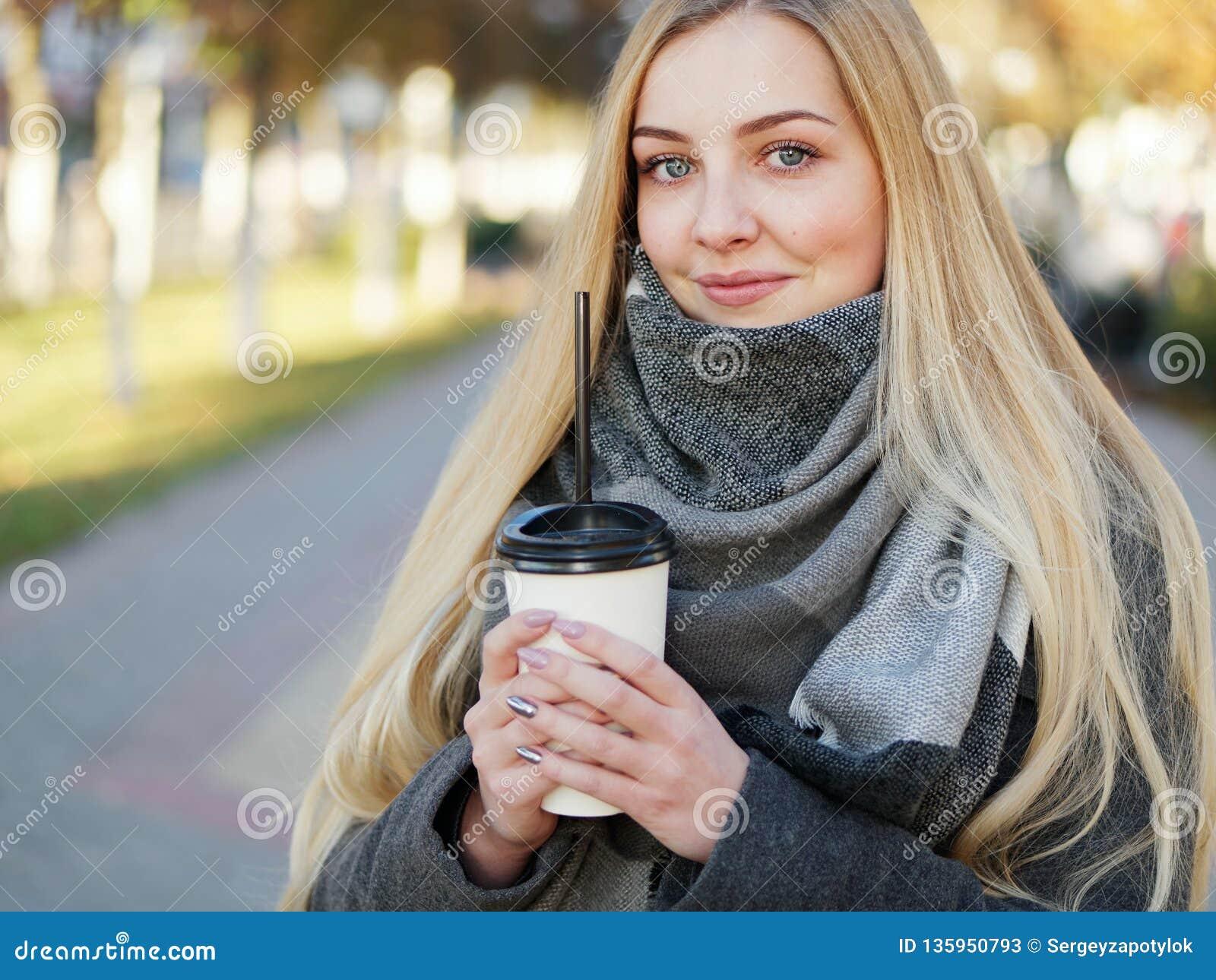 Fin extérieure vers le haut de tir de femme blonde élégante de l année 20s dans l écharpe sur le café ou le thé potable de pause
