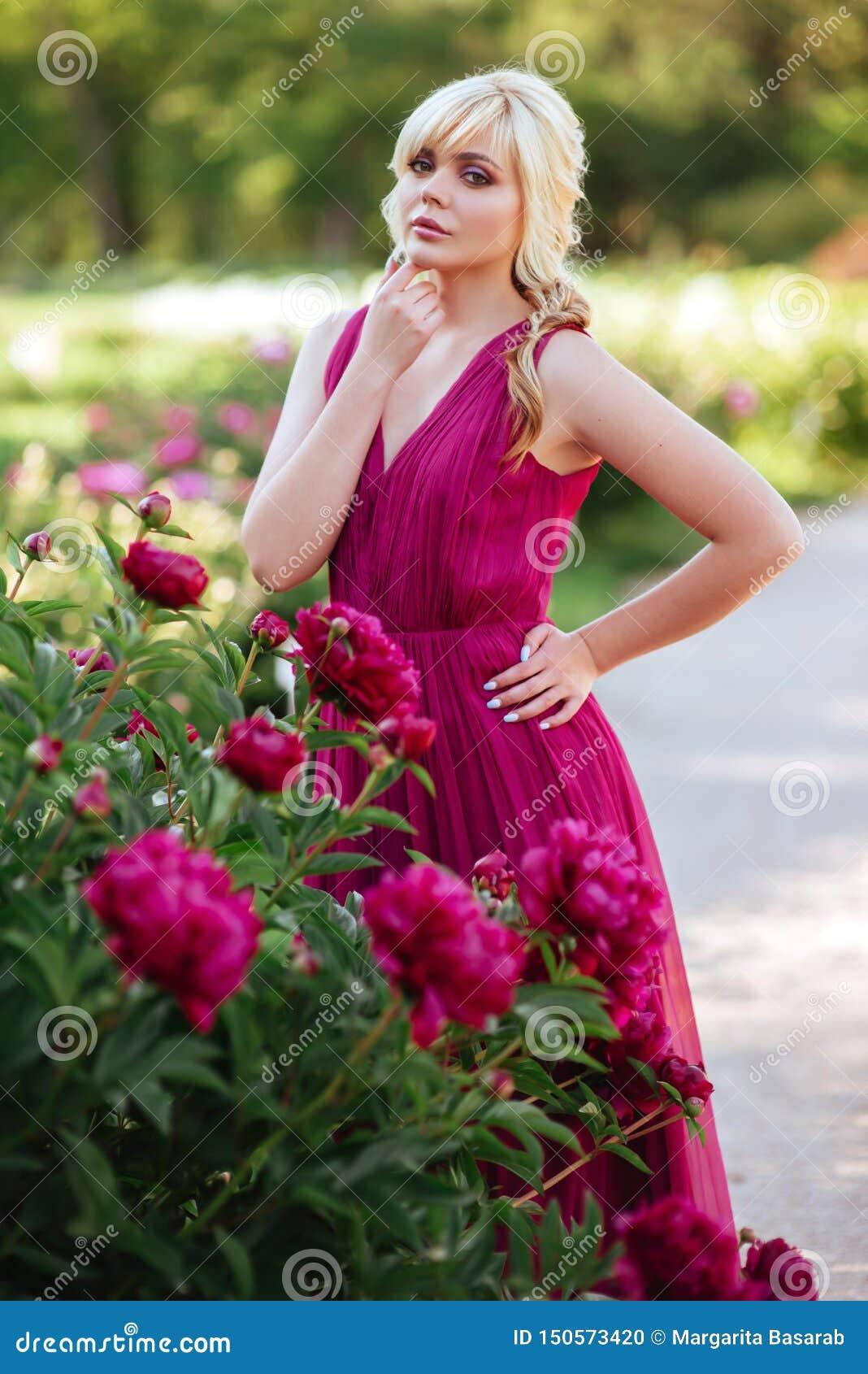 Fin ext?rieure vers le haut de portrait de belle jeune femme dans le jardin de floraison Concept femelle de mode de ressort