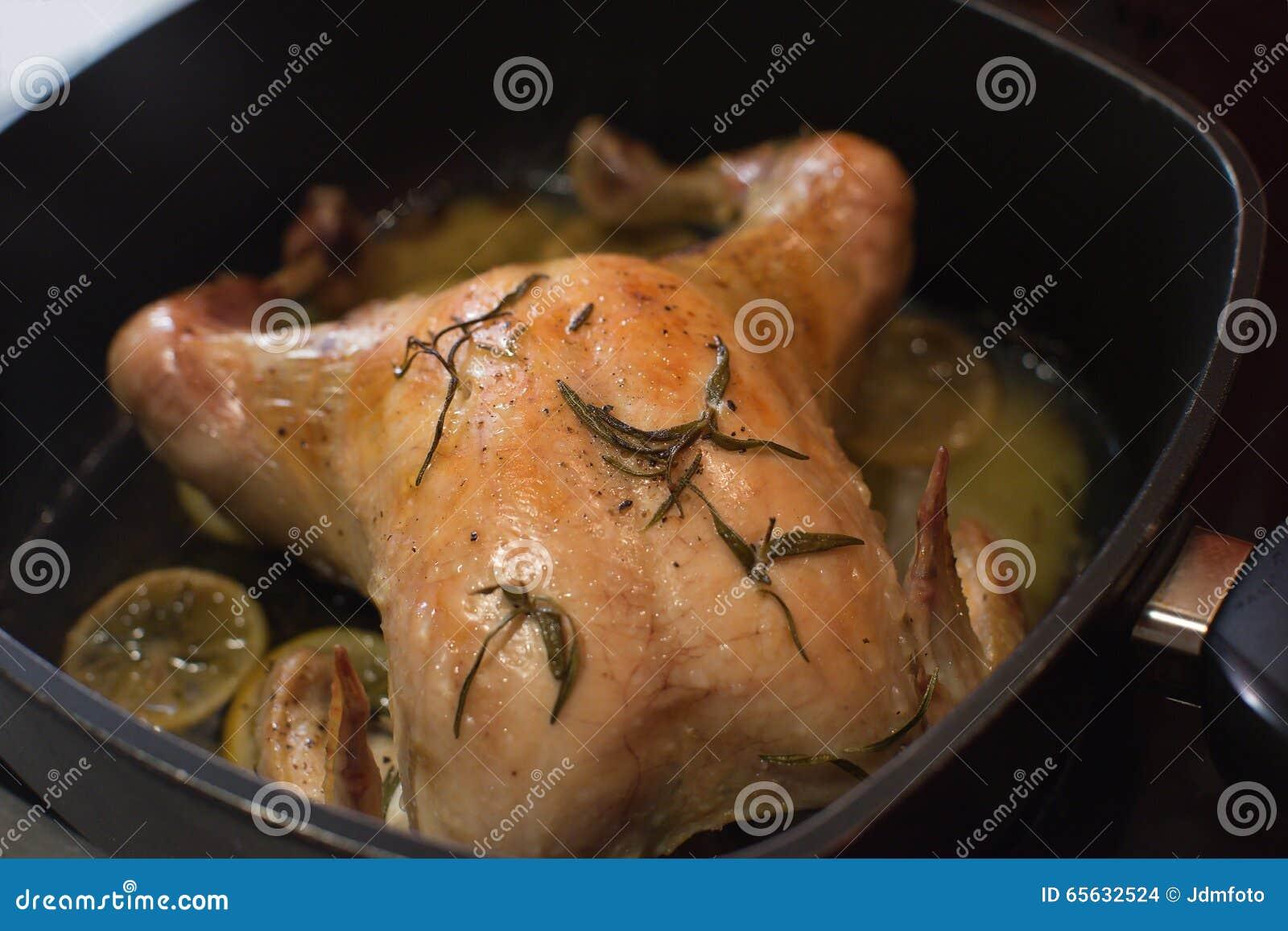 Fin rôtie de poulet entier dans la casserole de torréfaction avec des herbes de romarin, salées et se trouvantes sur les tranches