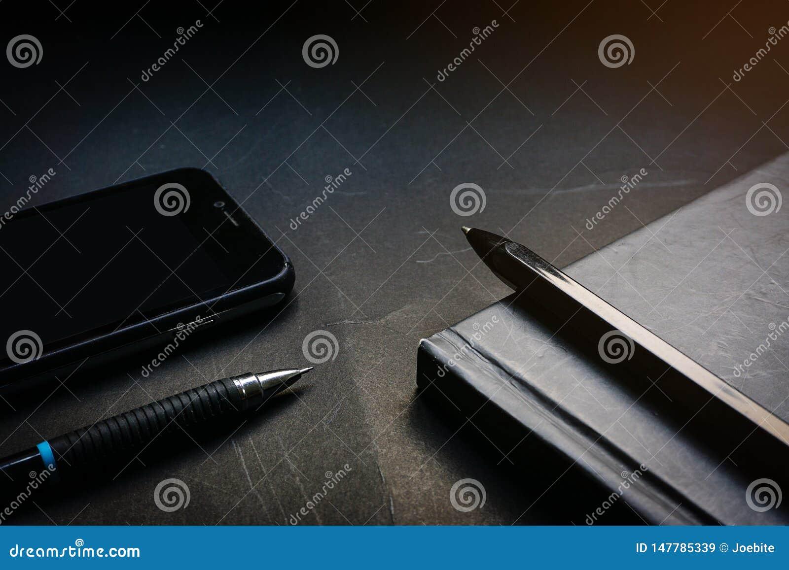 Fin vers le haut de carnet, de stylo, de crayon et de téléphone portable noirs sur le fond noir de bureau dans le ton de allumage
