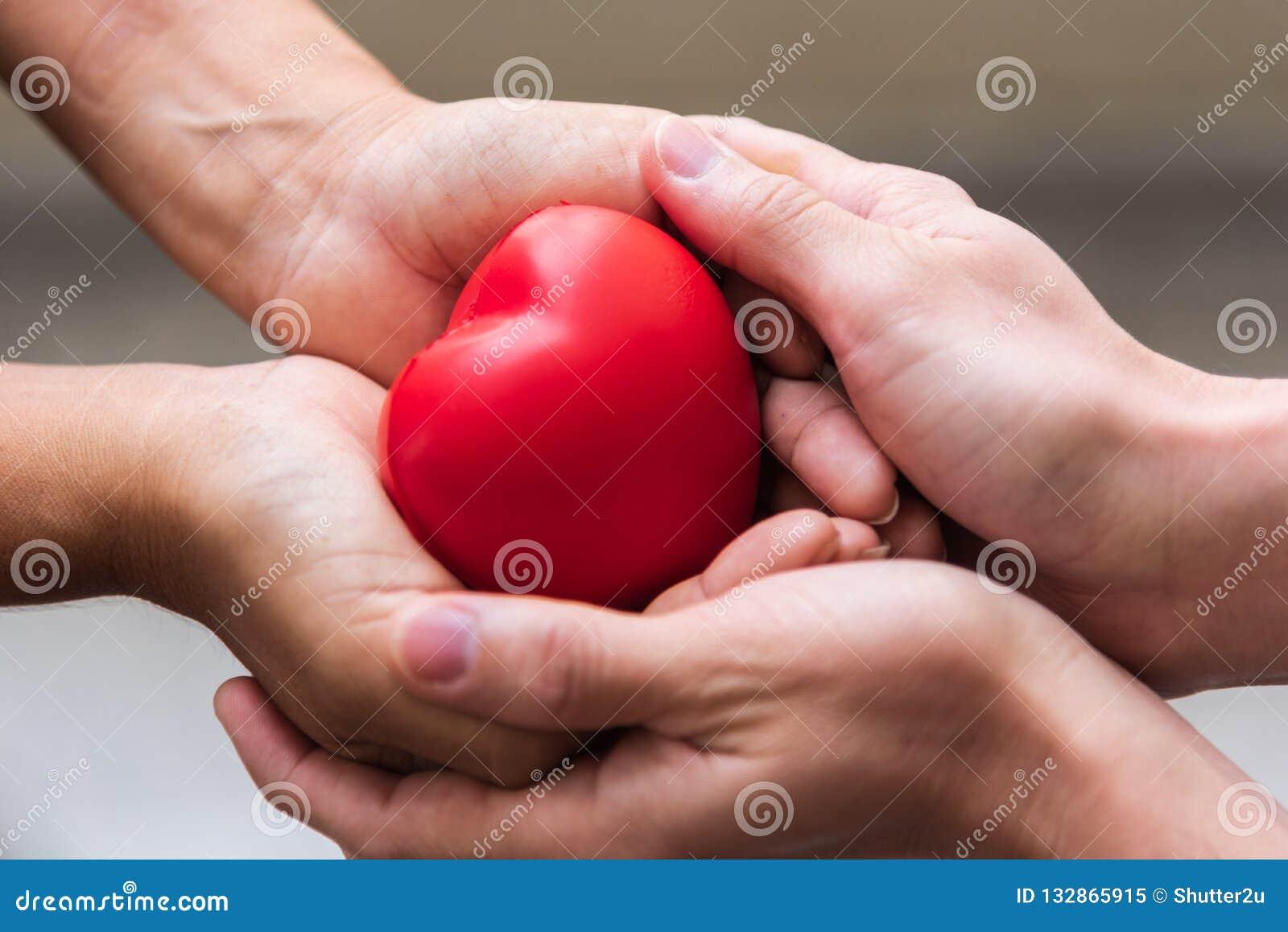 Fin vers le haut de la main donnant le coeur rouge comme donateur de coeur Saint Valentin de