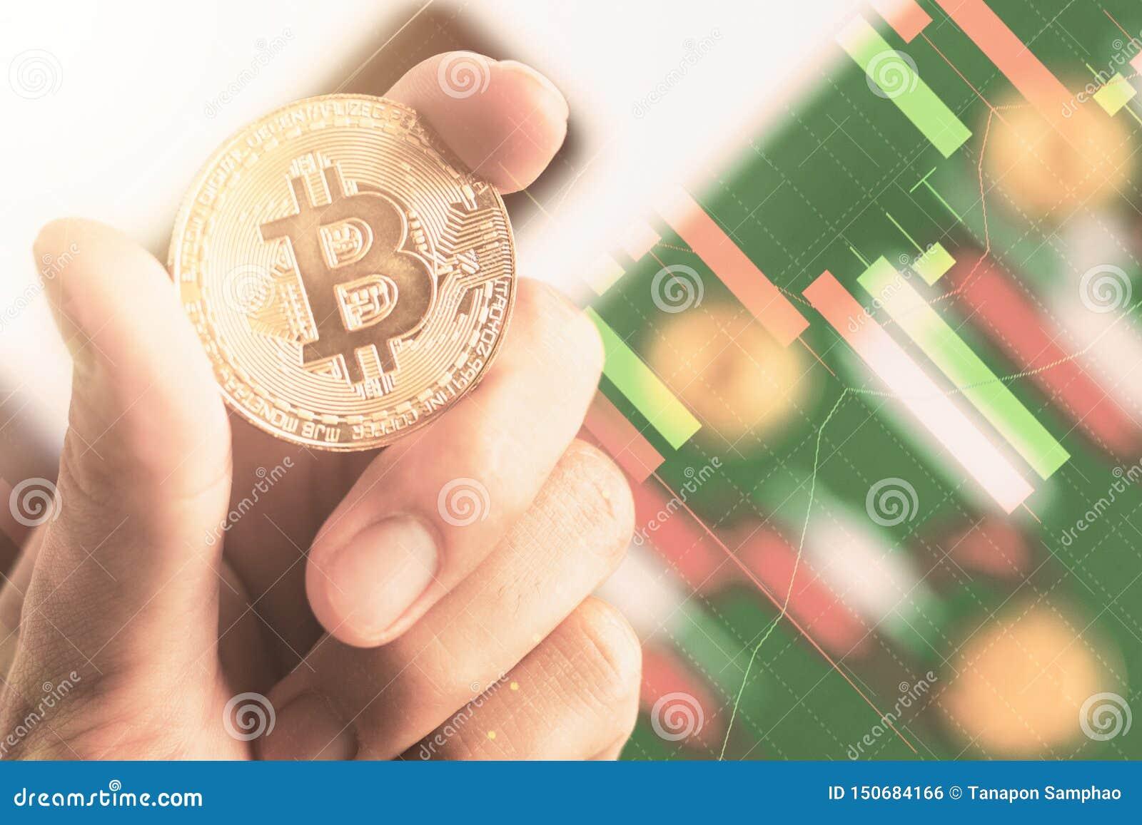 Fin vers le haut de la main tenant le bitcoin avec le diagramme de chandelier de fond