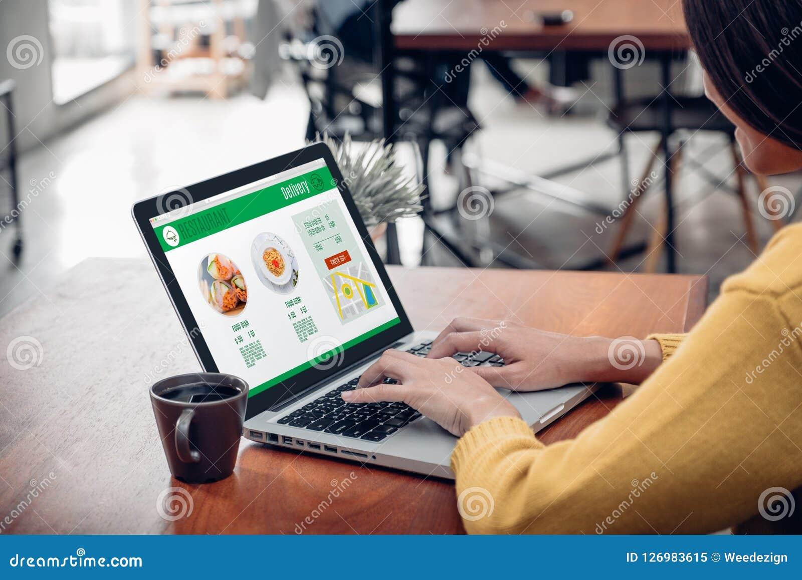 Fin vers le haut de nourriture de séance et d orde de femme en ligne sur l ordinateur portable i
