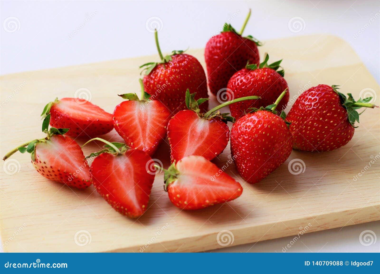 Fin vers le haut des fraises fraîches coupées dans la moitié et des fraises entières sur la planche à découper