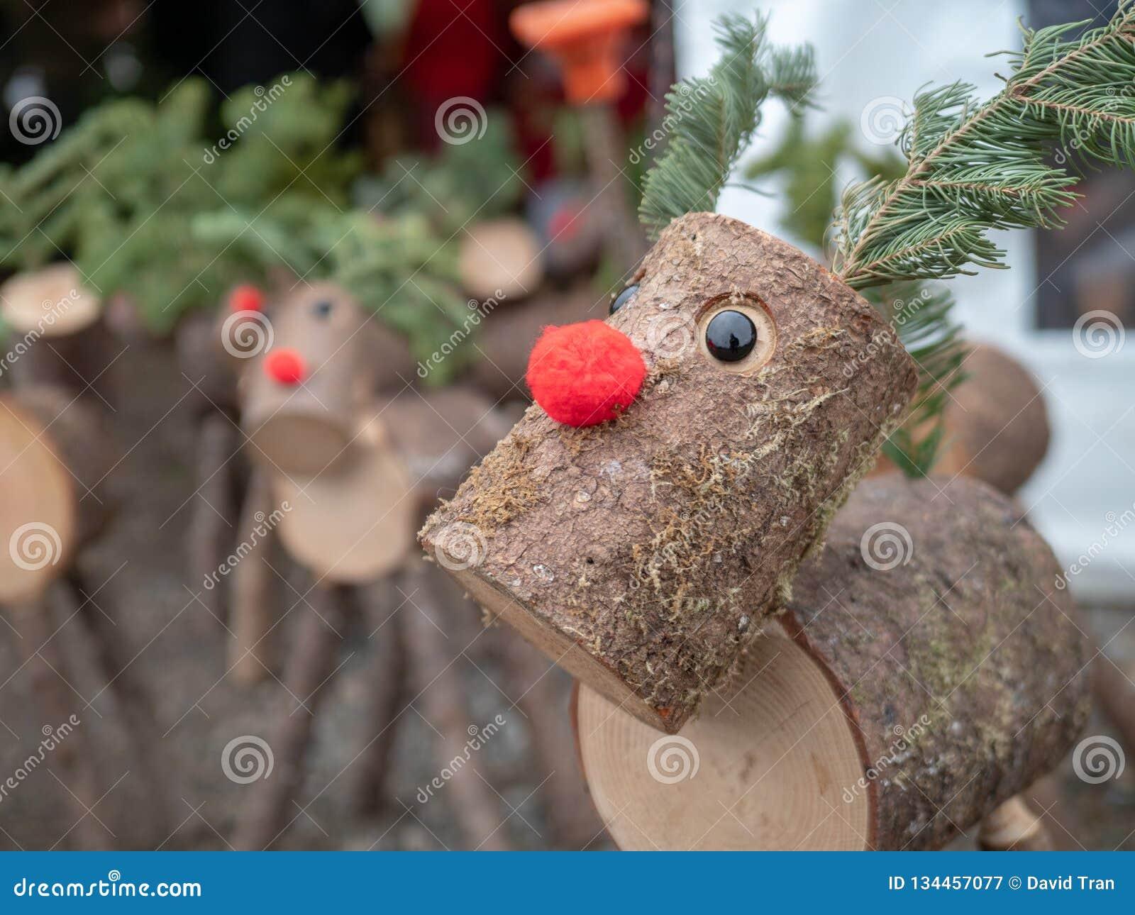 Fin vers le haut des versions en bois de rondin de temps flairé rouge de vacances de Noël de renne de Rudolph