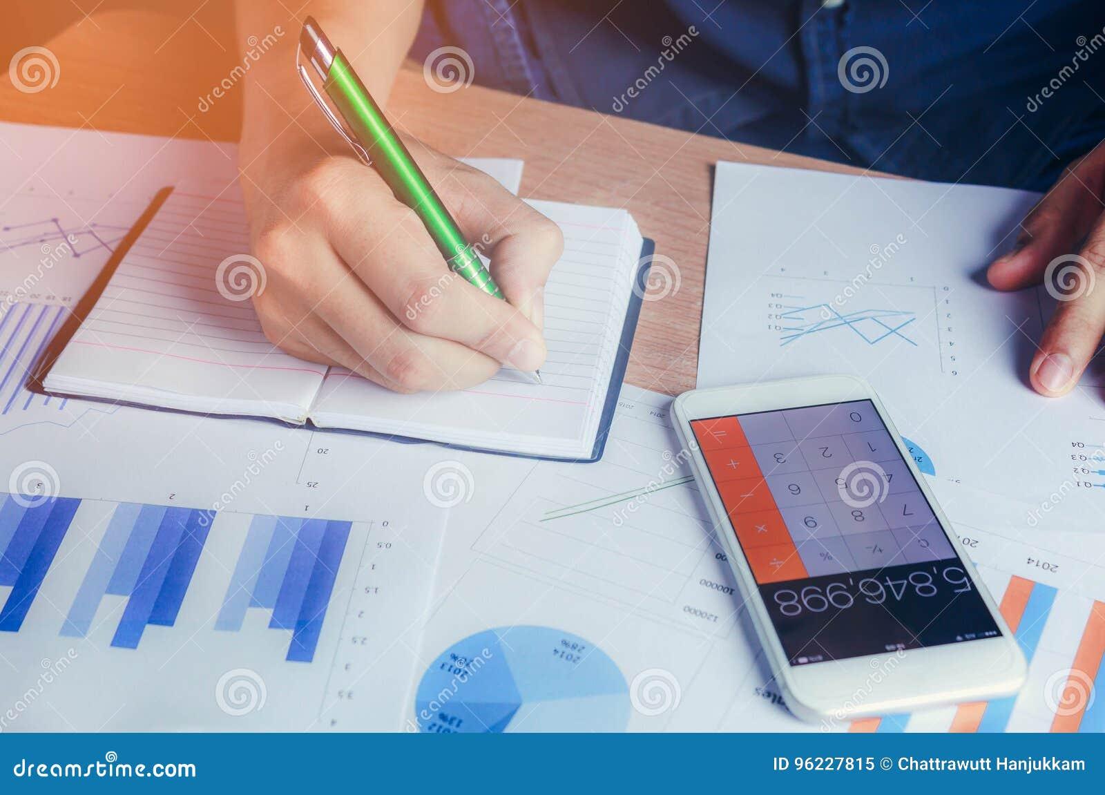 Finança calculadora e economia da mão asiática com telefone celular no fundo de madeira da tabela