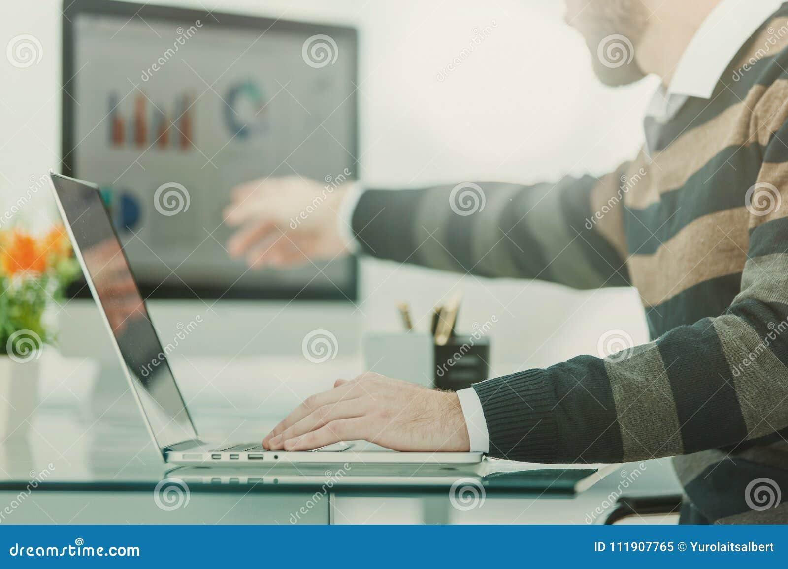 Financiënspecialist die aan laptop met financiële grafieken en marketing regelingen werken