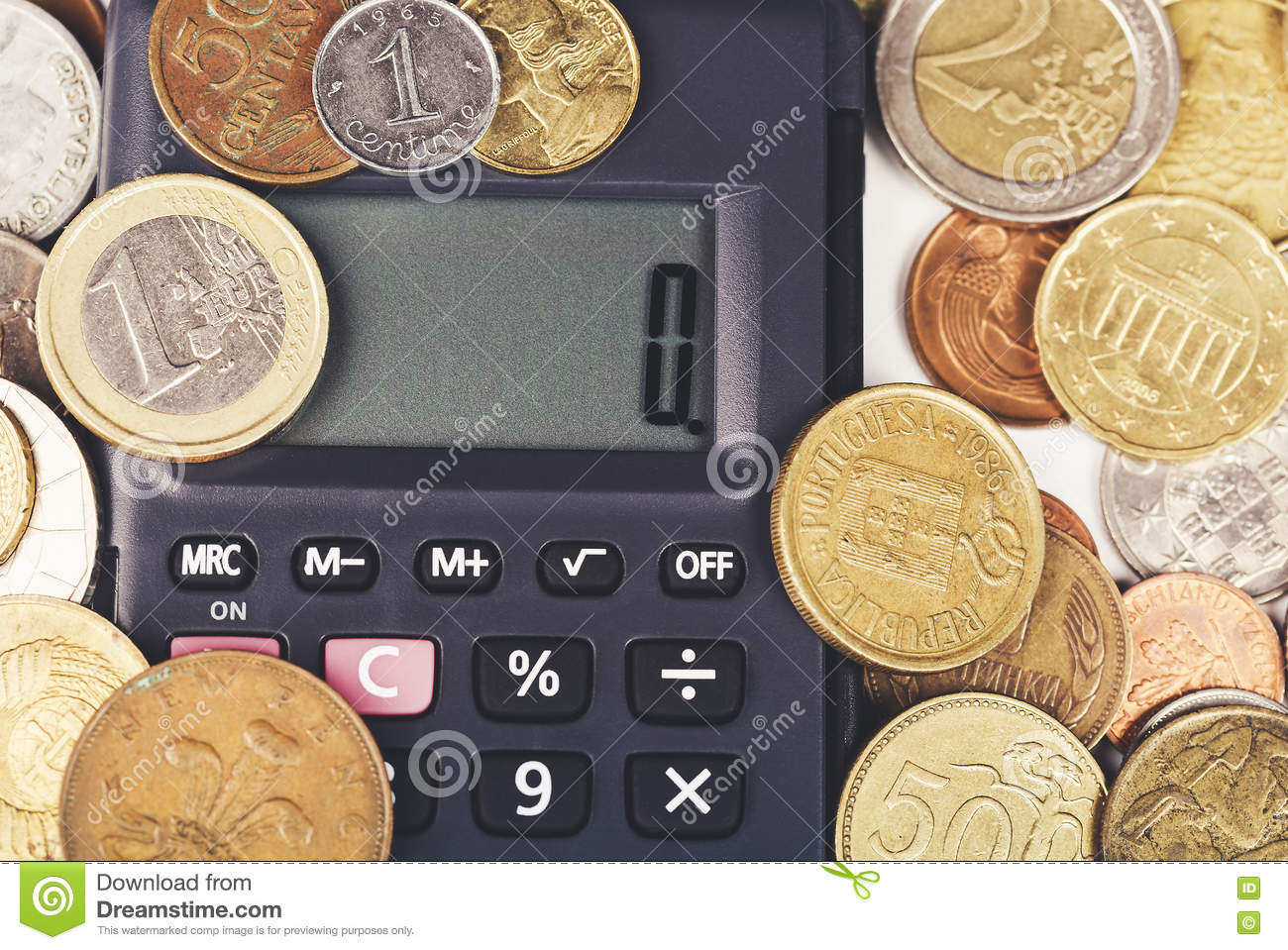 Financial concept. Calculator surrounded by various world currency coins closeup