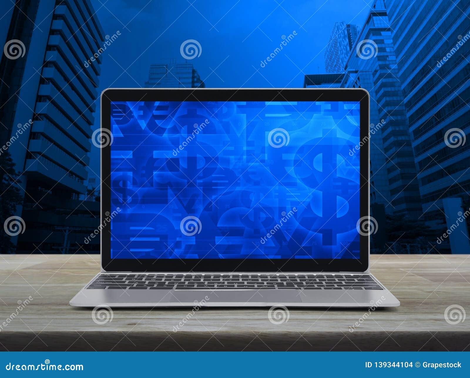 Financieel valutasymbool op het moderne laptop computerscherm op houten lijst over de toren en de wolkenkrabber van de bureaustad