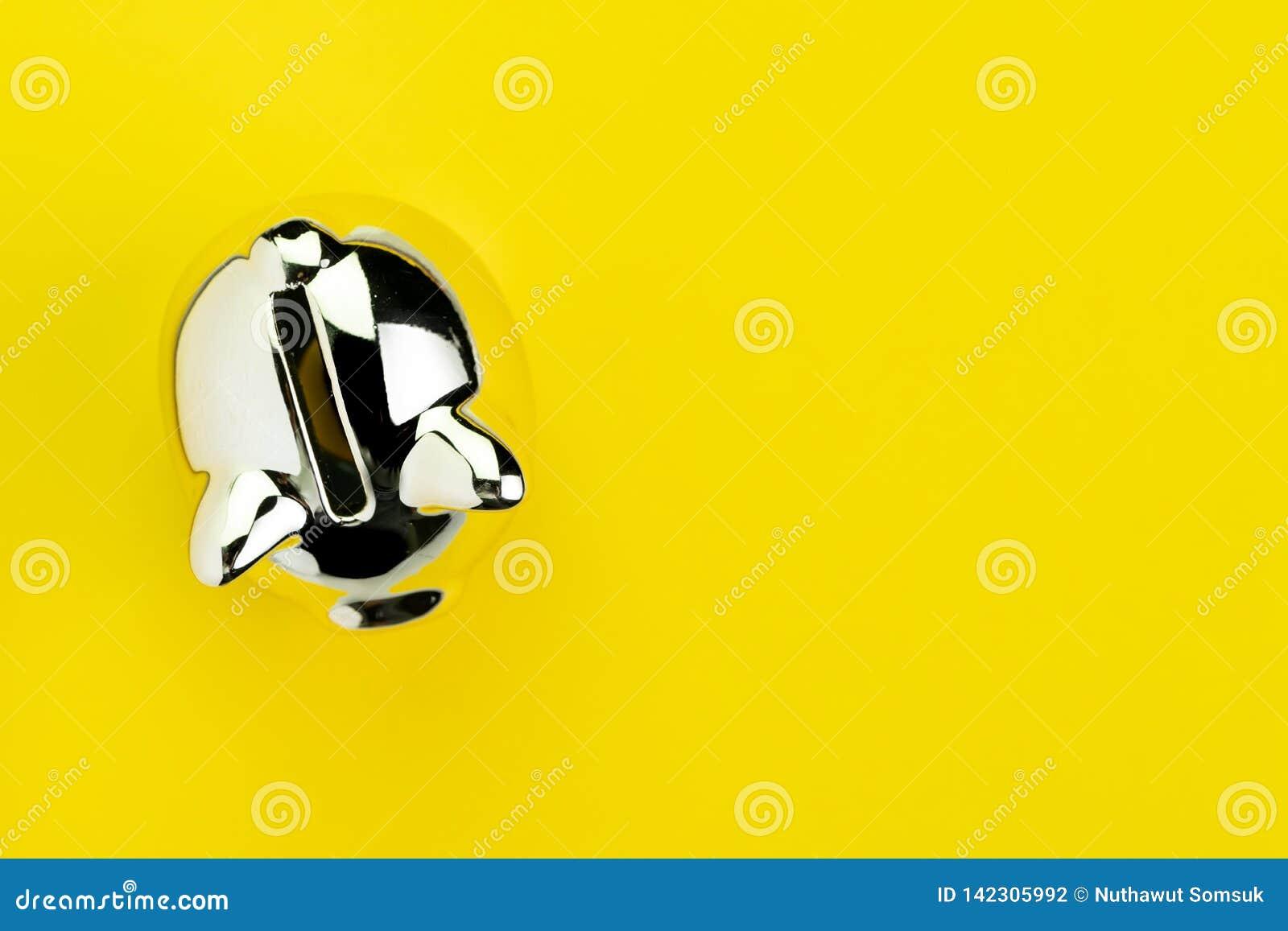 Finans, bankrörelsen, besparingar eller investeringbegreppet som är skinande försilvrar spargrisen på fast gul bakgrund med kopie
