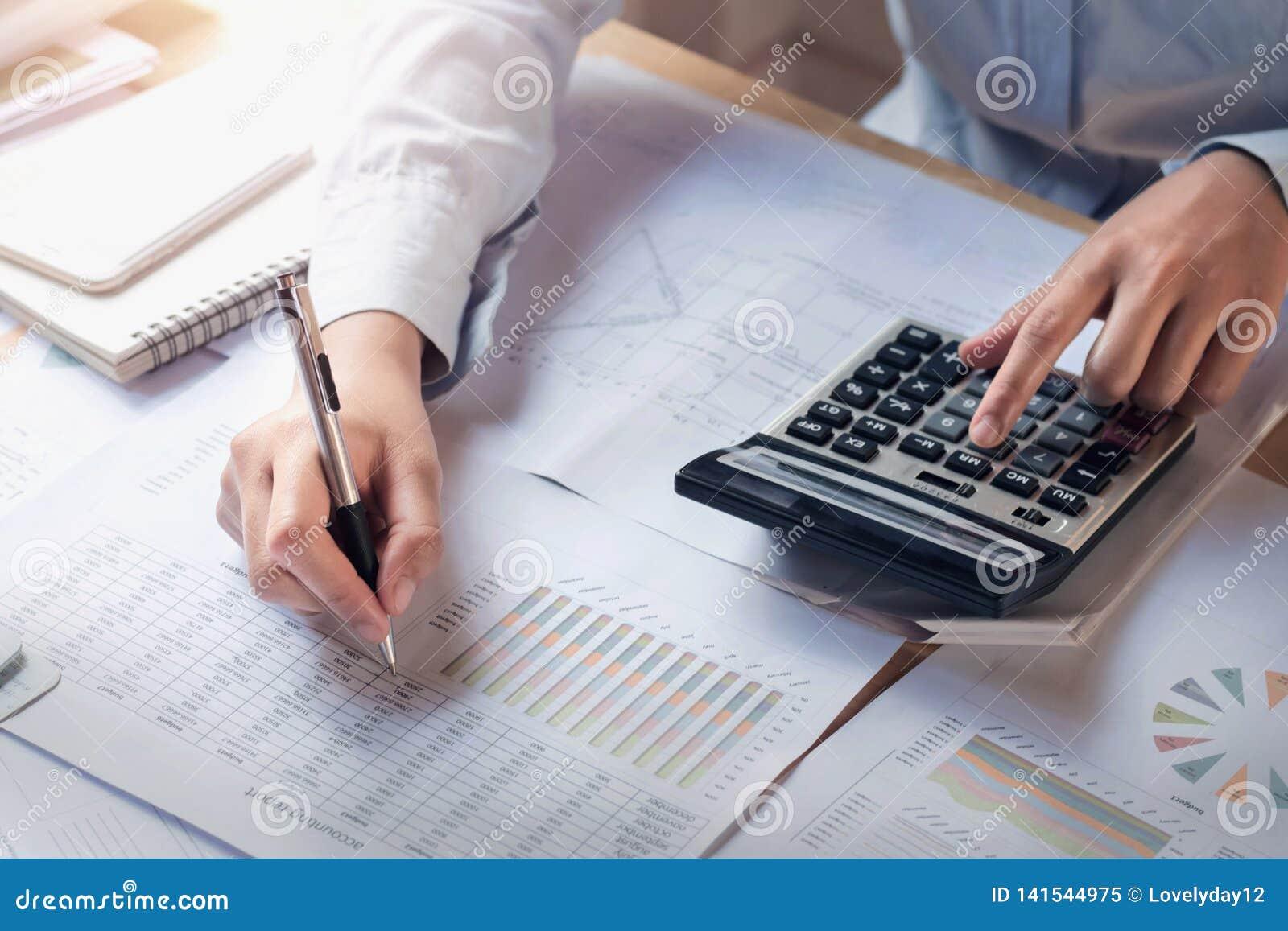 Finans och redogöra begrepp affärskvinna som arbetar på skrivbordet genom att använda räknemaskinen för att beräkna
