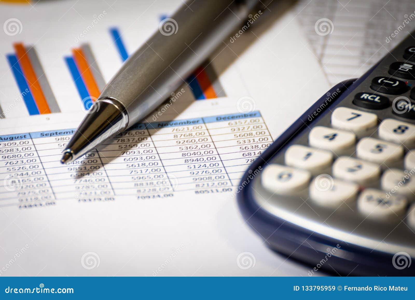 Finans, planläggning för affärsbudget och analysbegrepp, grafrapport med räknemaskinen på kontorsskrivbordet