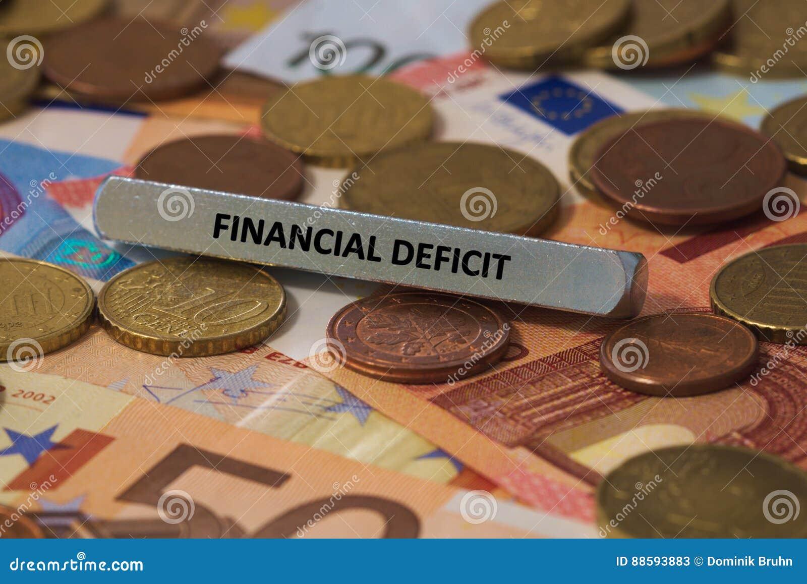 Finansiellt underskott - ordet skrivevs ut på en metallstång metallstången förlades på flera sedlar