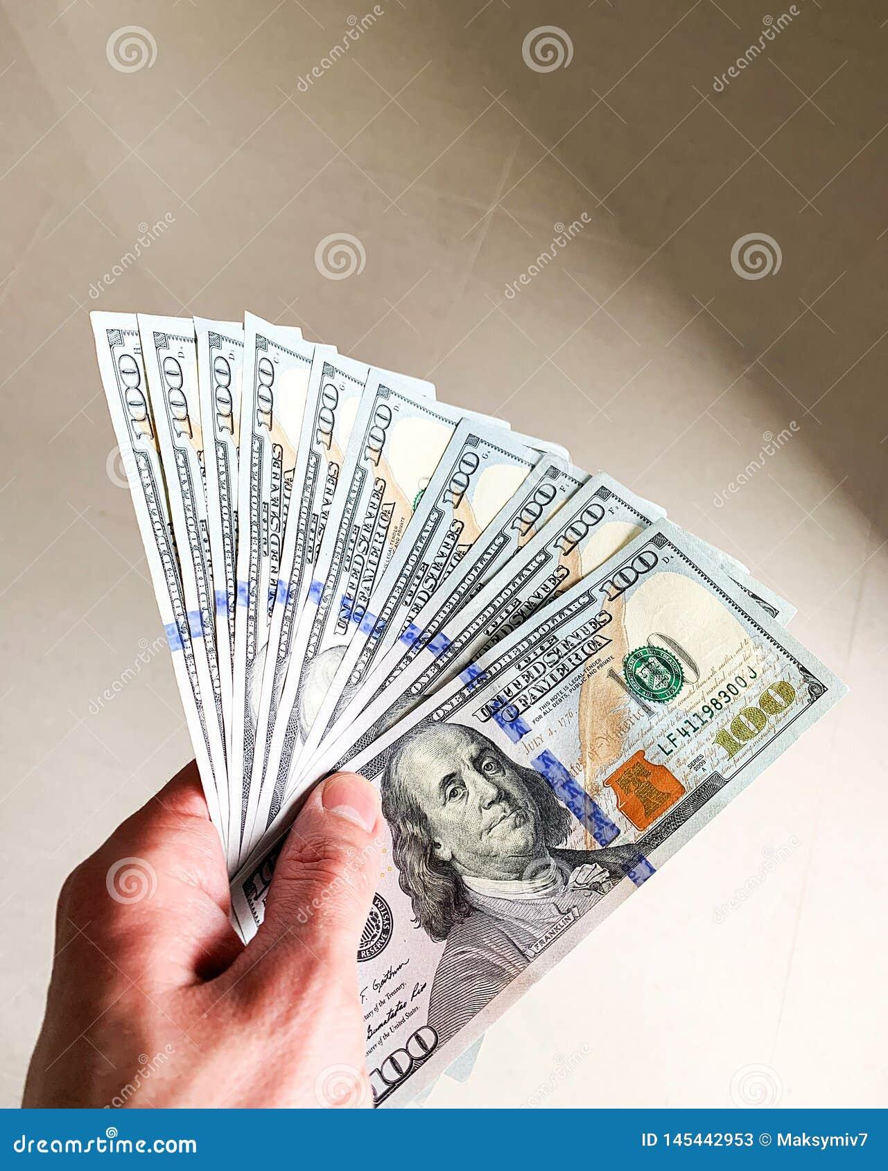 Finansowy pieni?dze Zbli?enie trzyma dolary r?ka