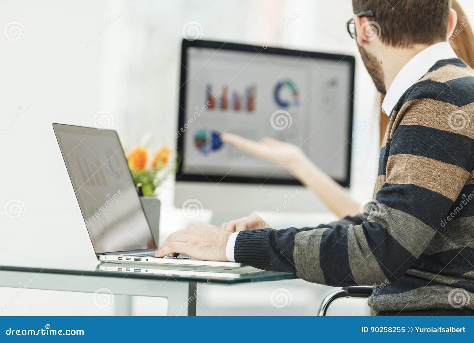 Finanzi lo specialista che lavora al computer portatile con i grafici e gli schemi finanziari di vendita
