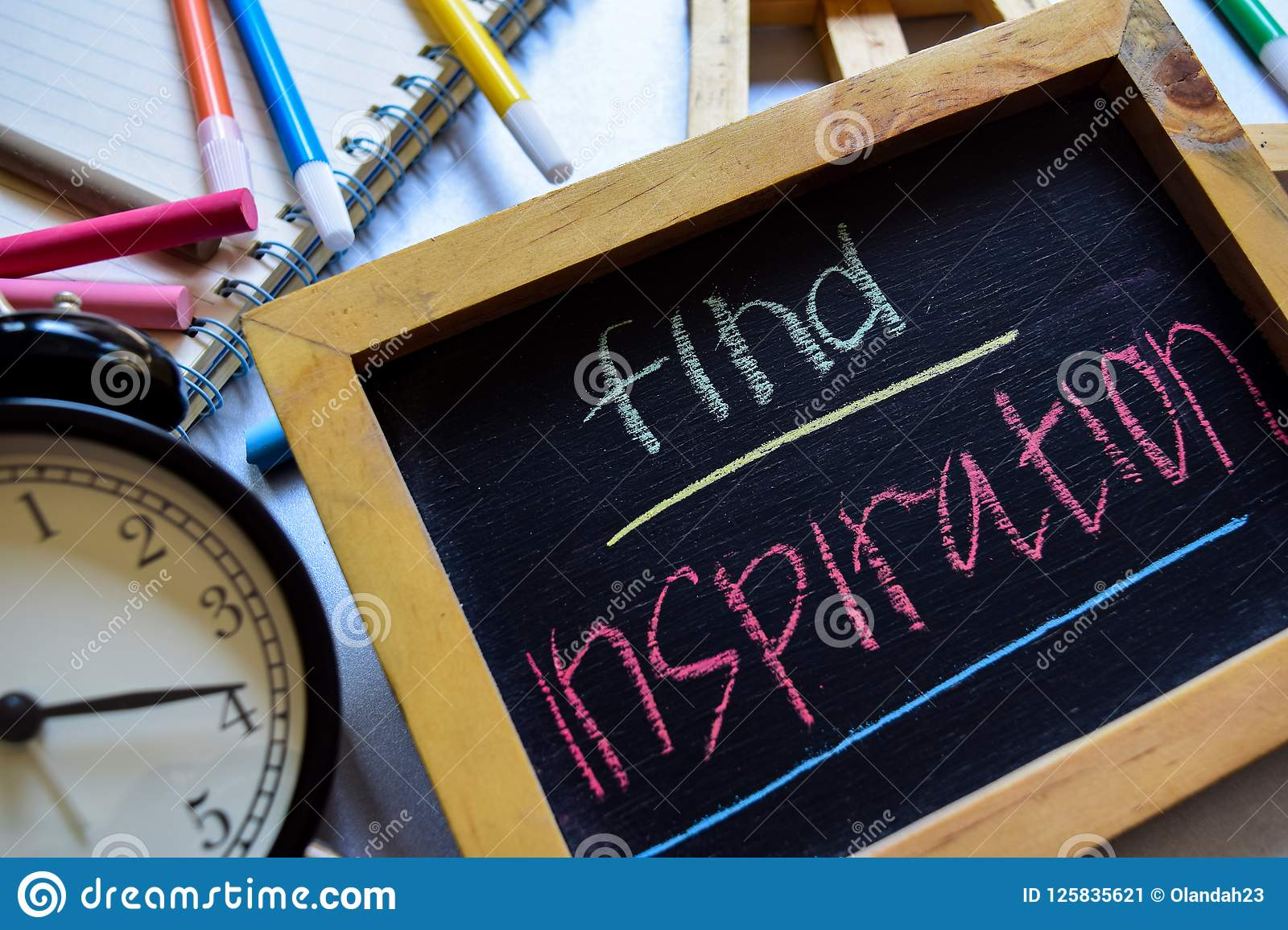 Find inspiration on phrase colorful handwritten on chalkboard, alarm clock with motivation and education concepts.